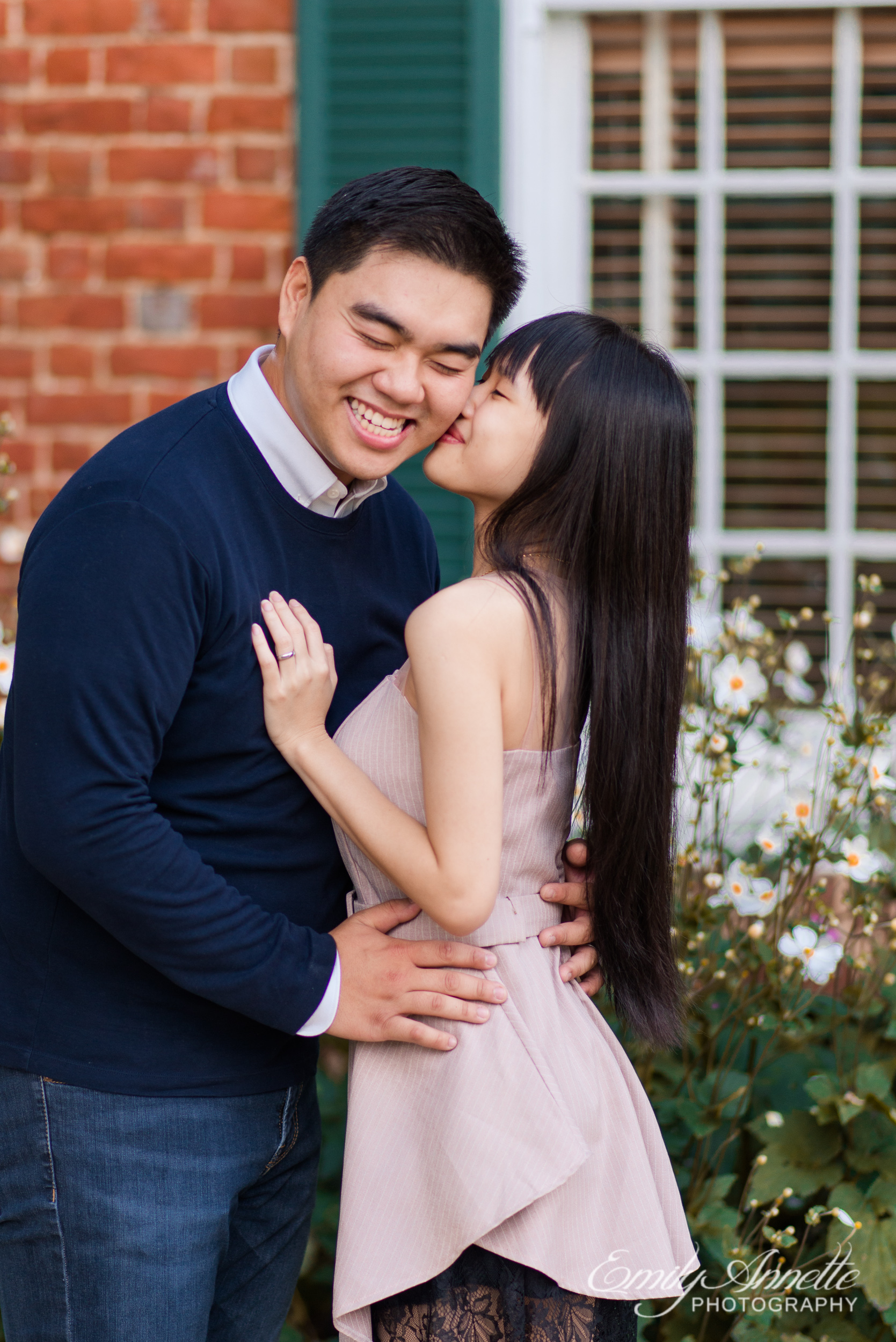 A young woman kisses her boyfriend's cheek outside the historic house at Green Spring Gardens Park in Fairfax, Virginia