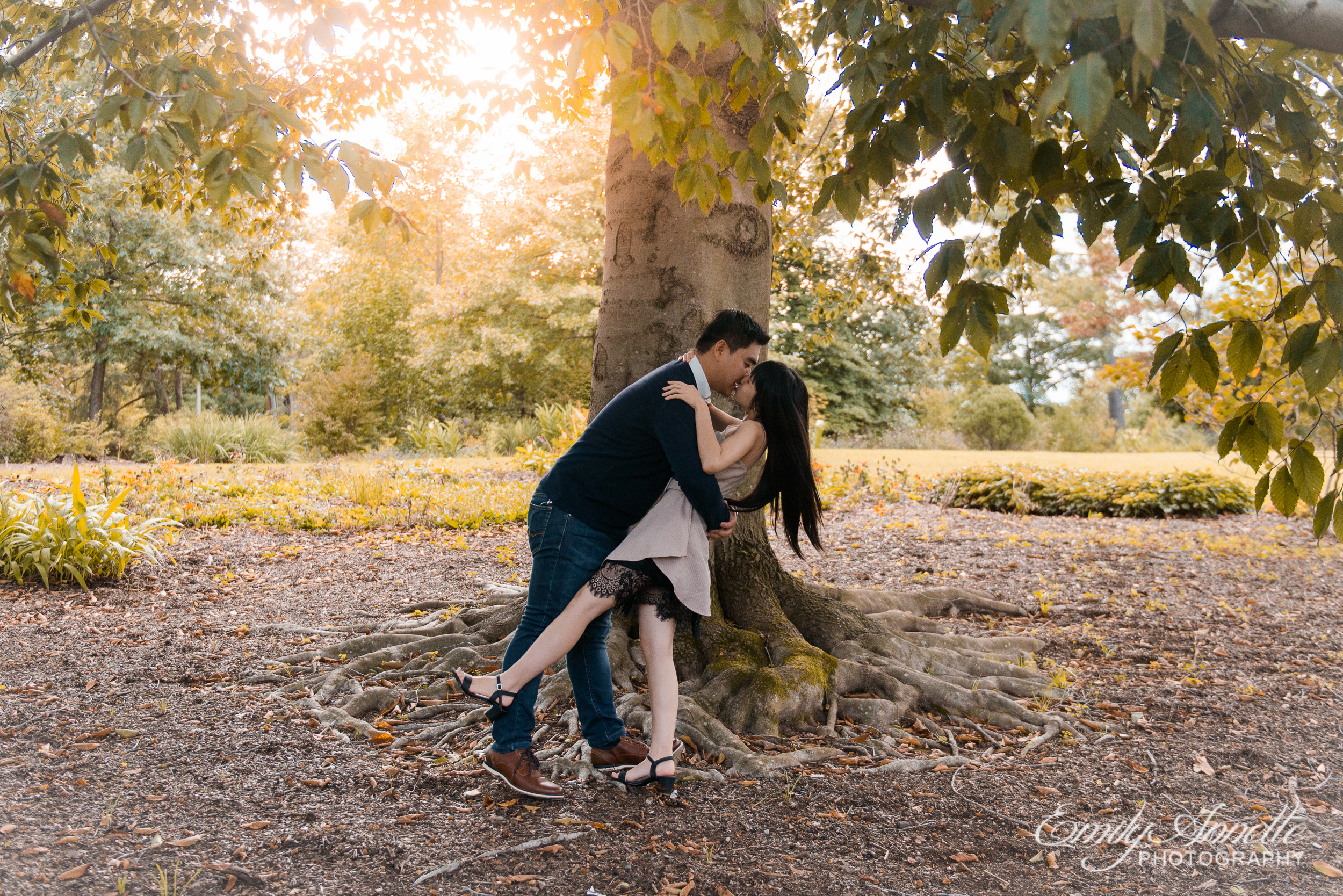 A young couple dip for a dramatic kiss beside a tree at Green Spring Gardens Park in Fairfax, Virginia