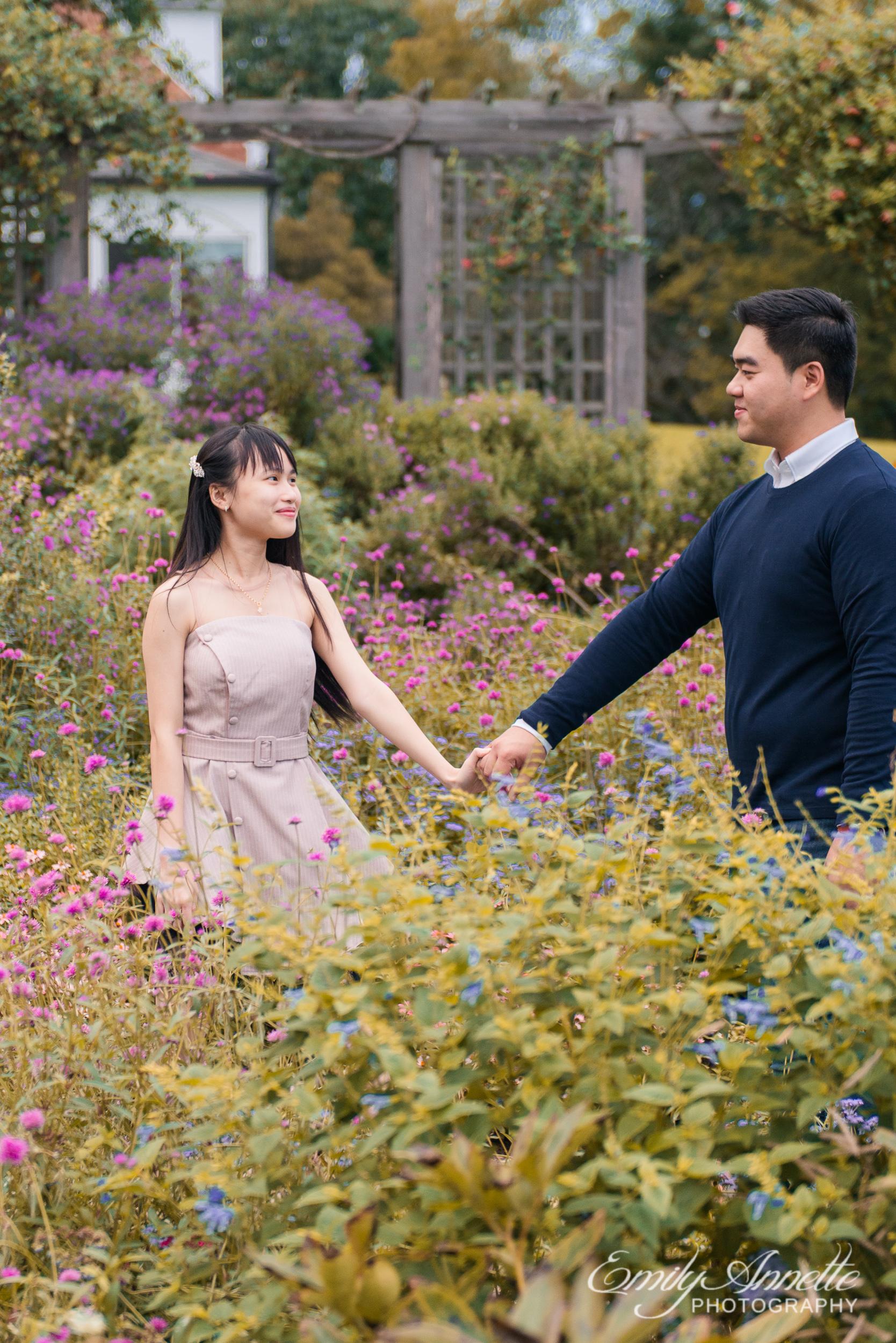 A young couple hold hands and walk through the garden at Green Spring Gardens Park in Fairfax, Virginia