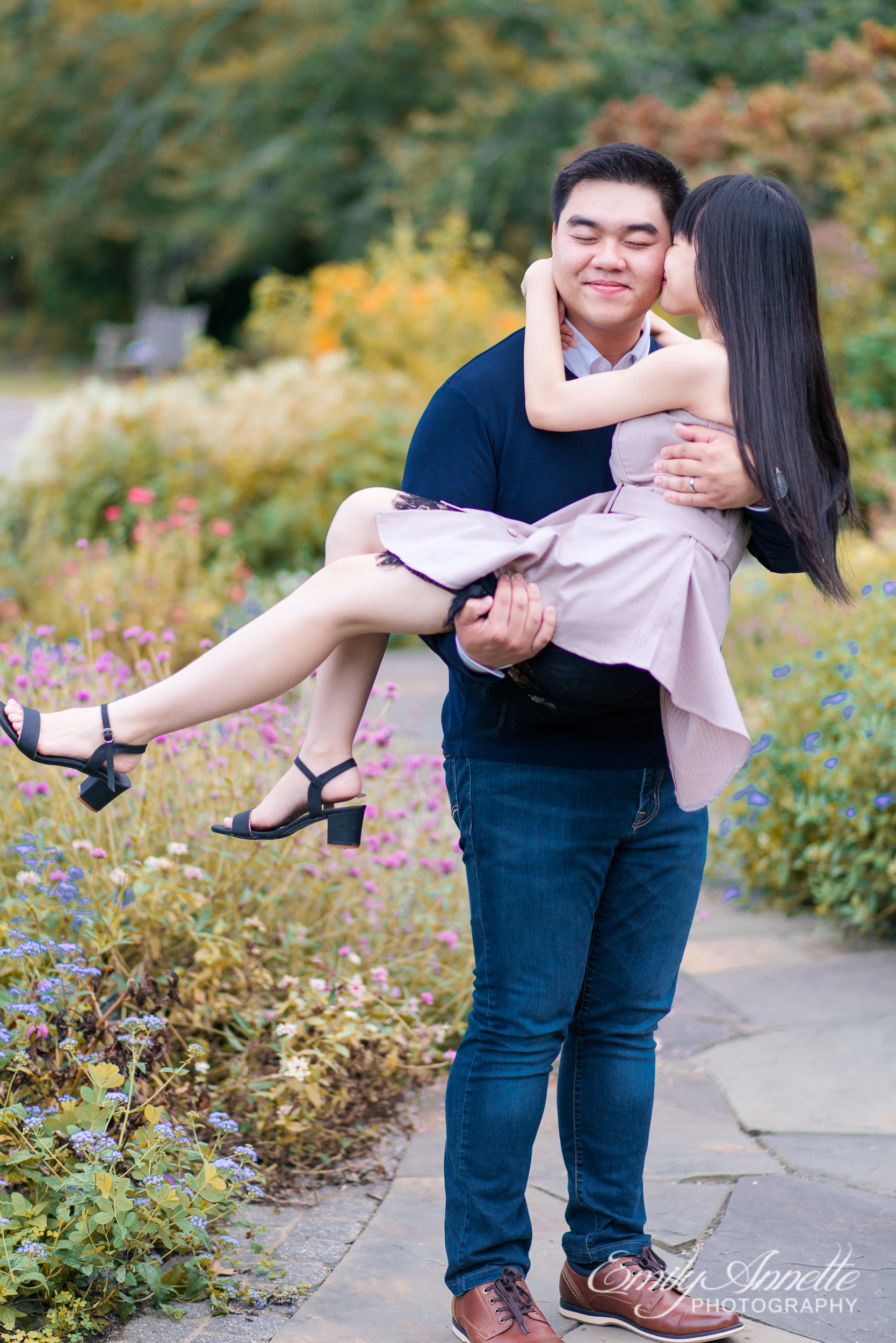 A young man lifts his girlfriend off the ground and carries her as she kisses his cheek in the garden at Green Spring Gardens Park in Fairfax, Virginia
