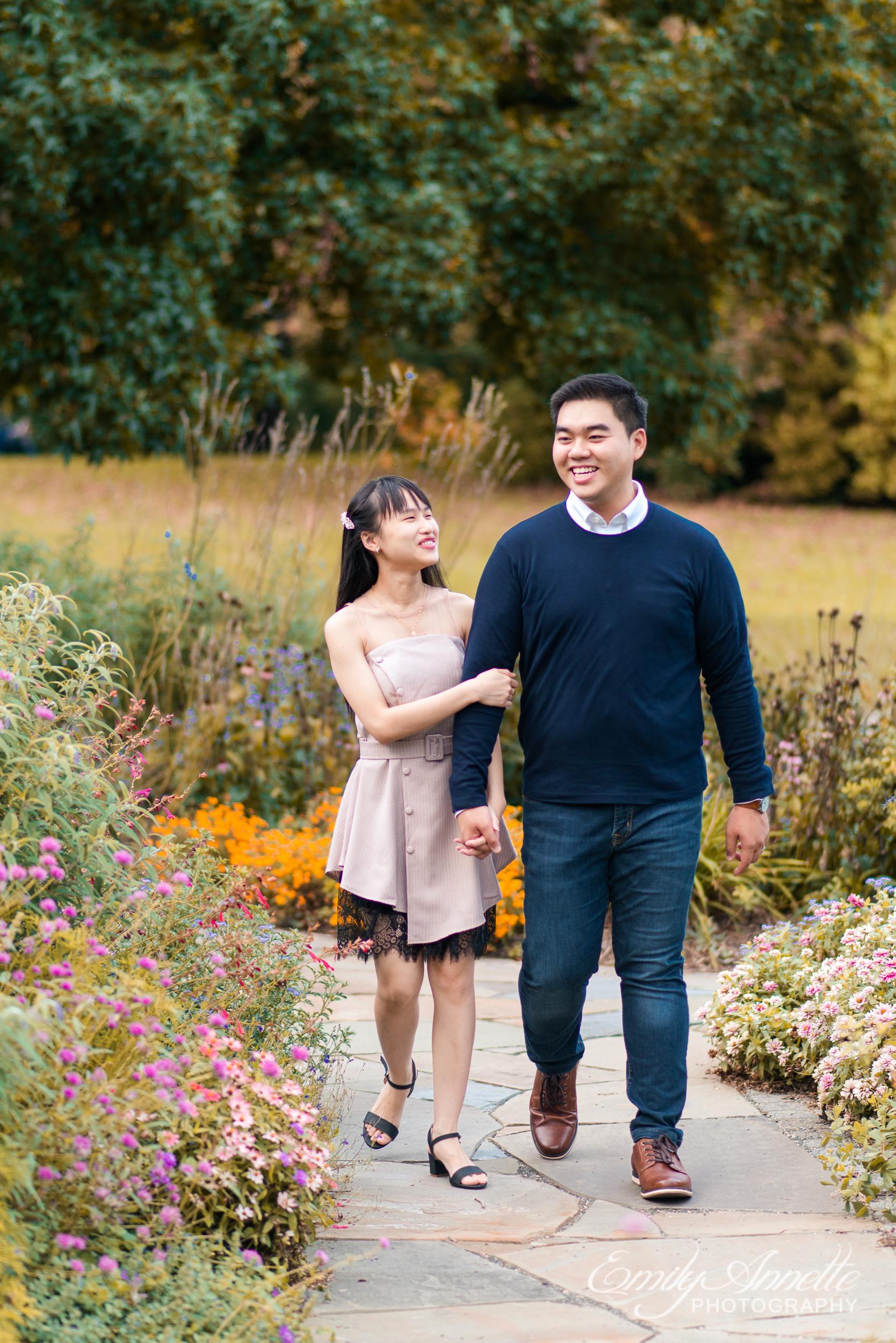 A young couple walk down a path through the garden at Green Spring Gardens Park in Fairfax, Virginia