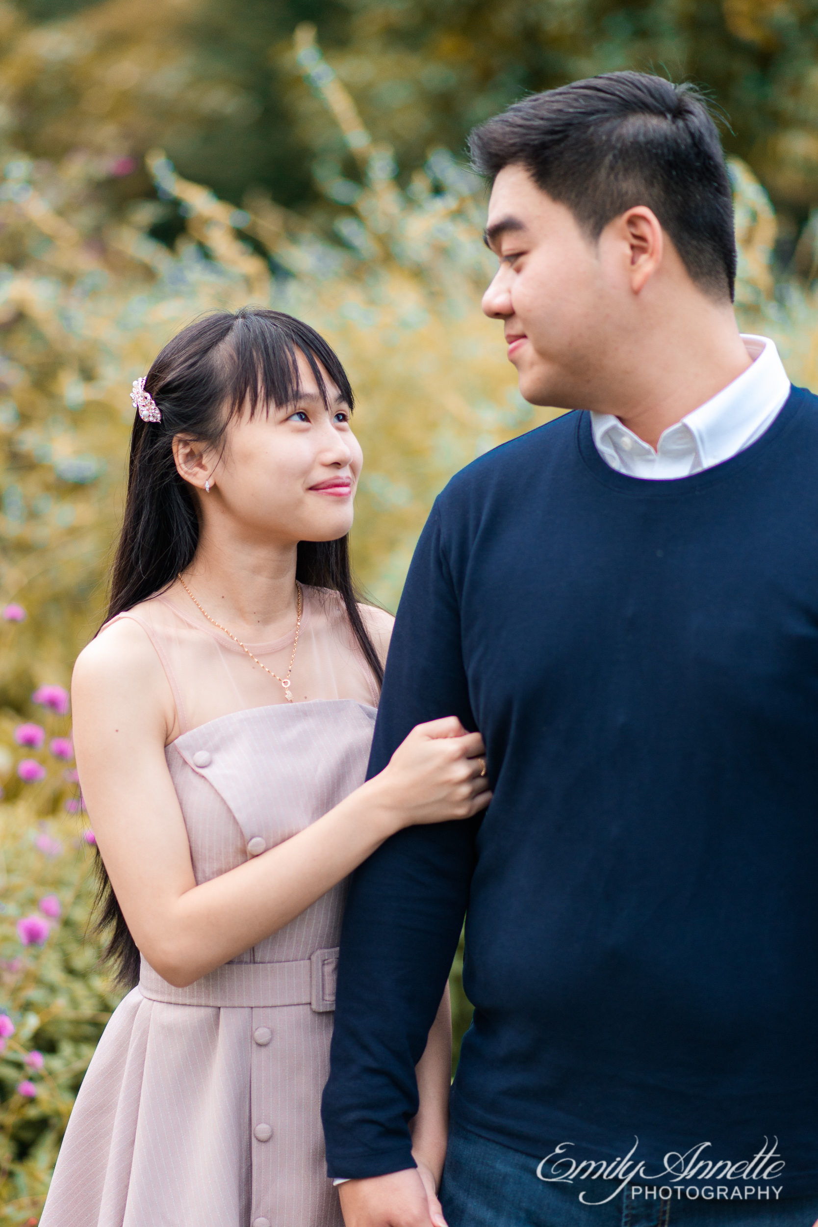 A young woman holds her boyfriend's arm and looks up at him in the garden at Green Spring Gardens Park in Fairfax, Virginia
