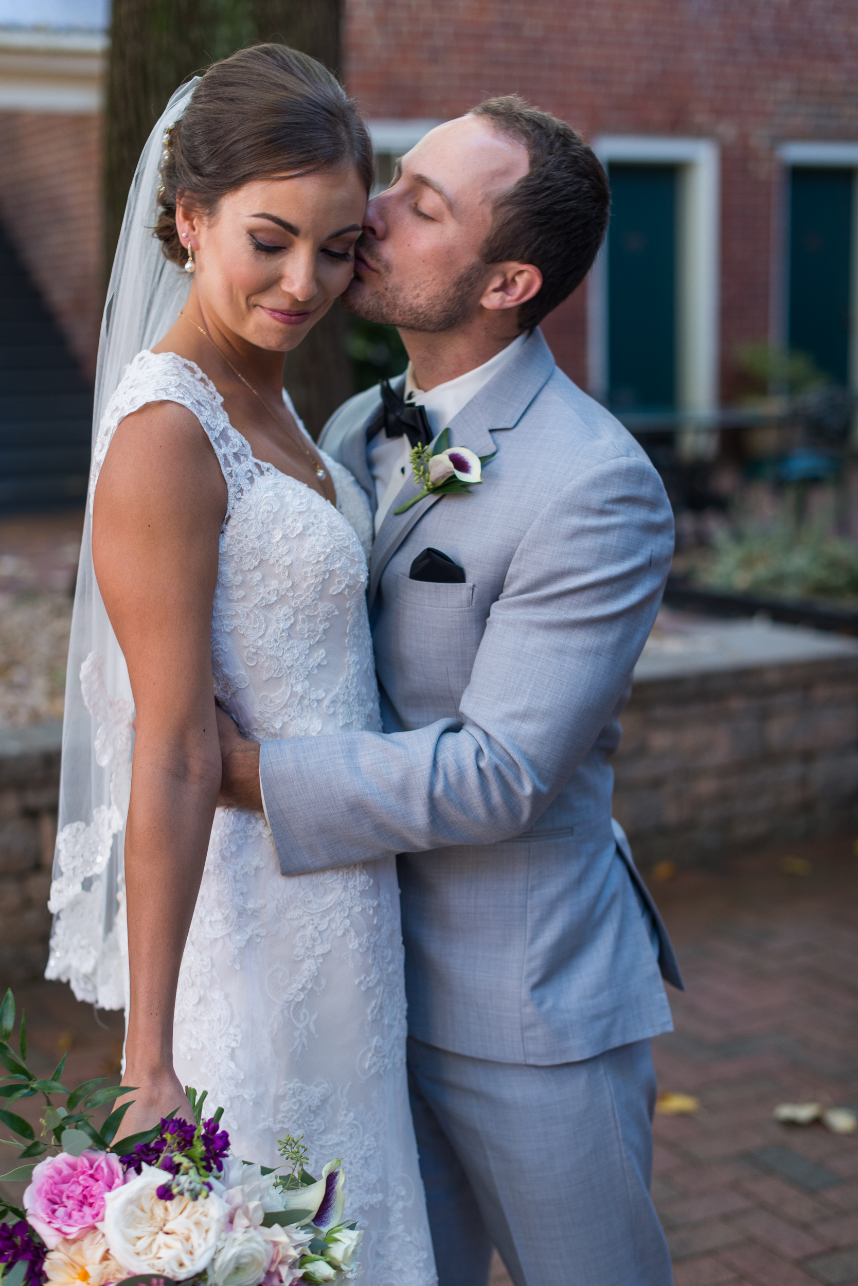 A groom kisses his bride's temple and holds her waist after their wedding in fairfax, virginia