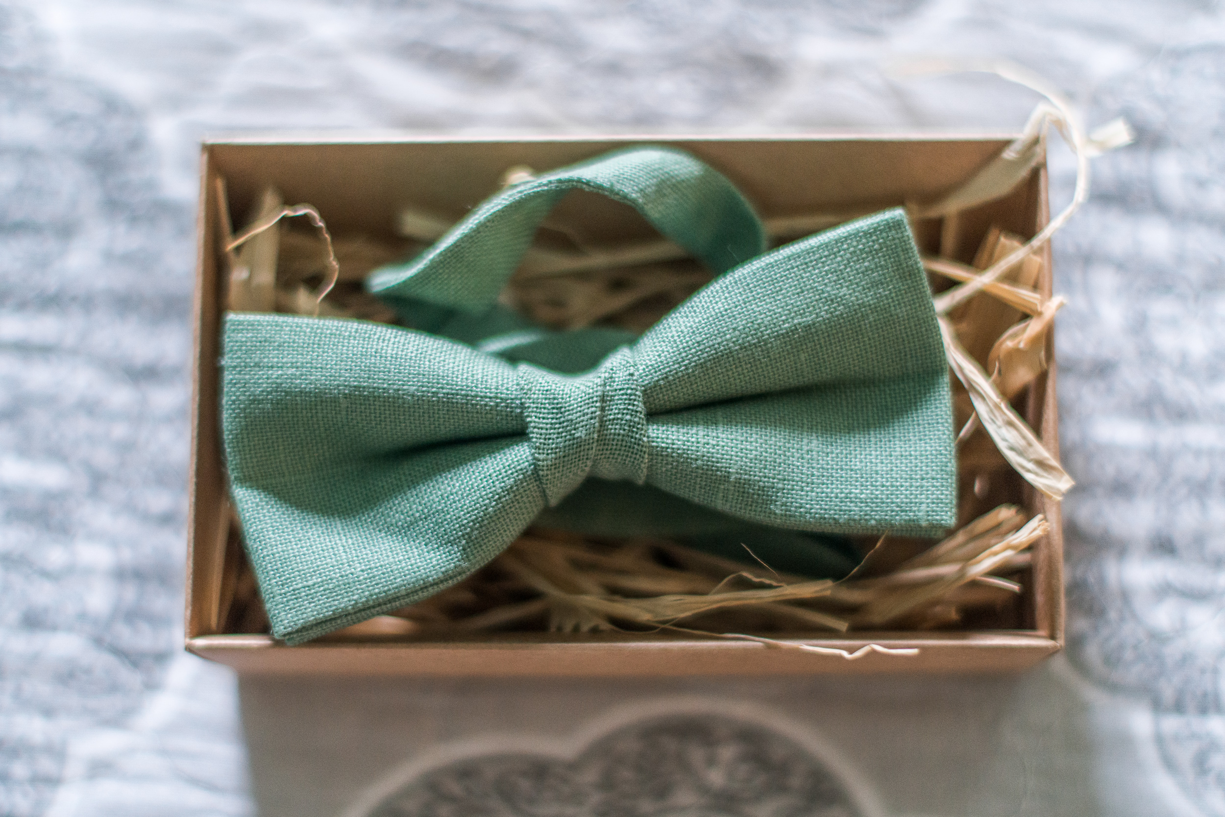 A green cotton bowtie for the groom before his wedding at St. Veronica Catholic Church in Chantilly, Virginia