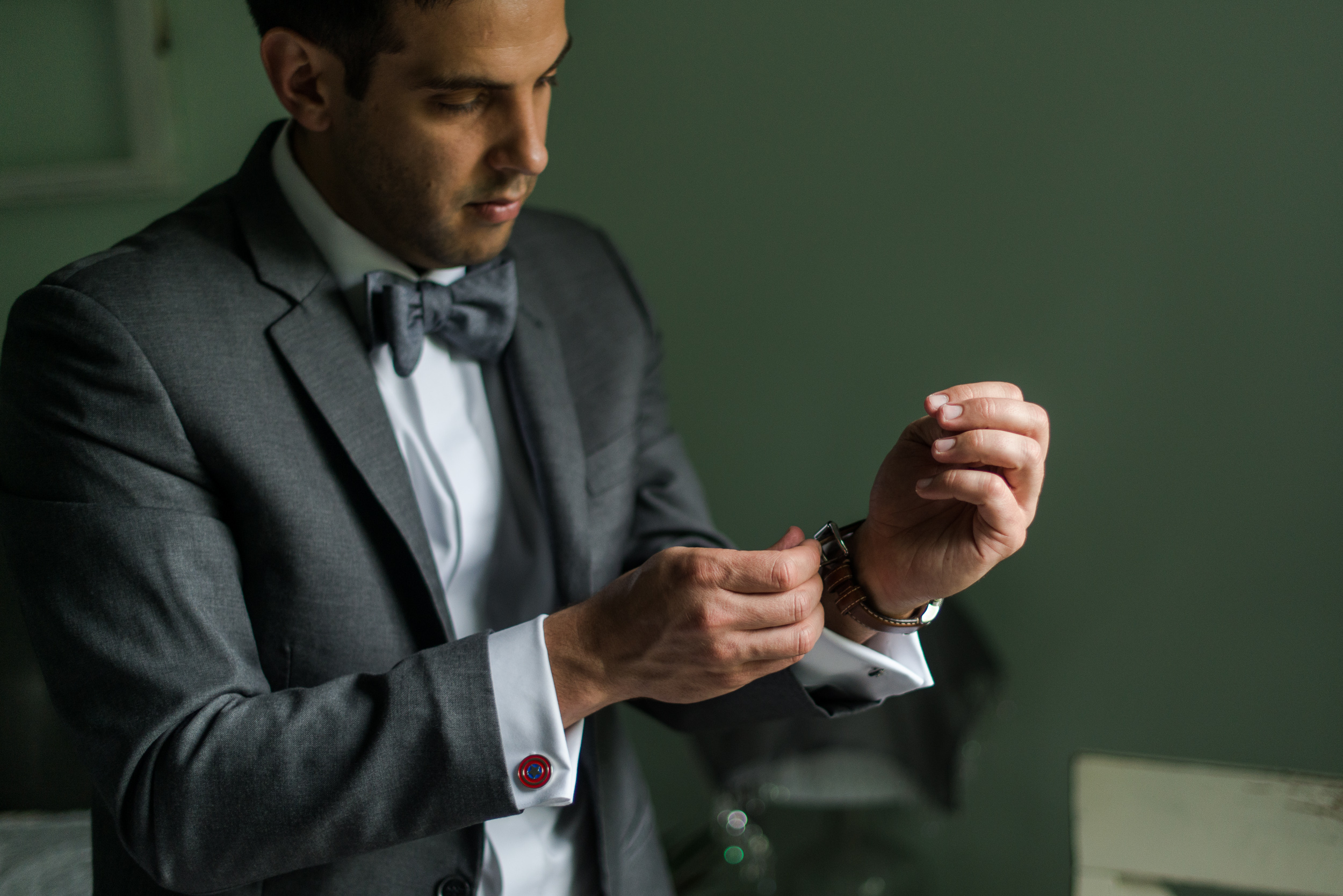 The groom puts on his watch and Captain America cufflinks before his wedding at St. Veronica Catholic Church in Chantilly, Virginia
