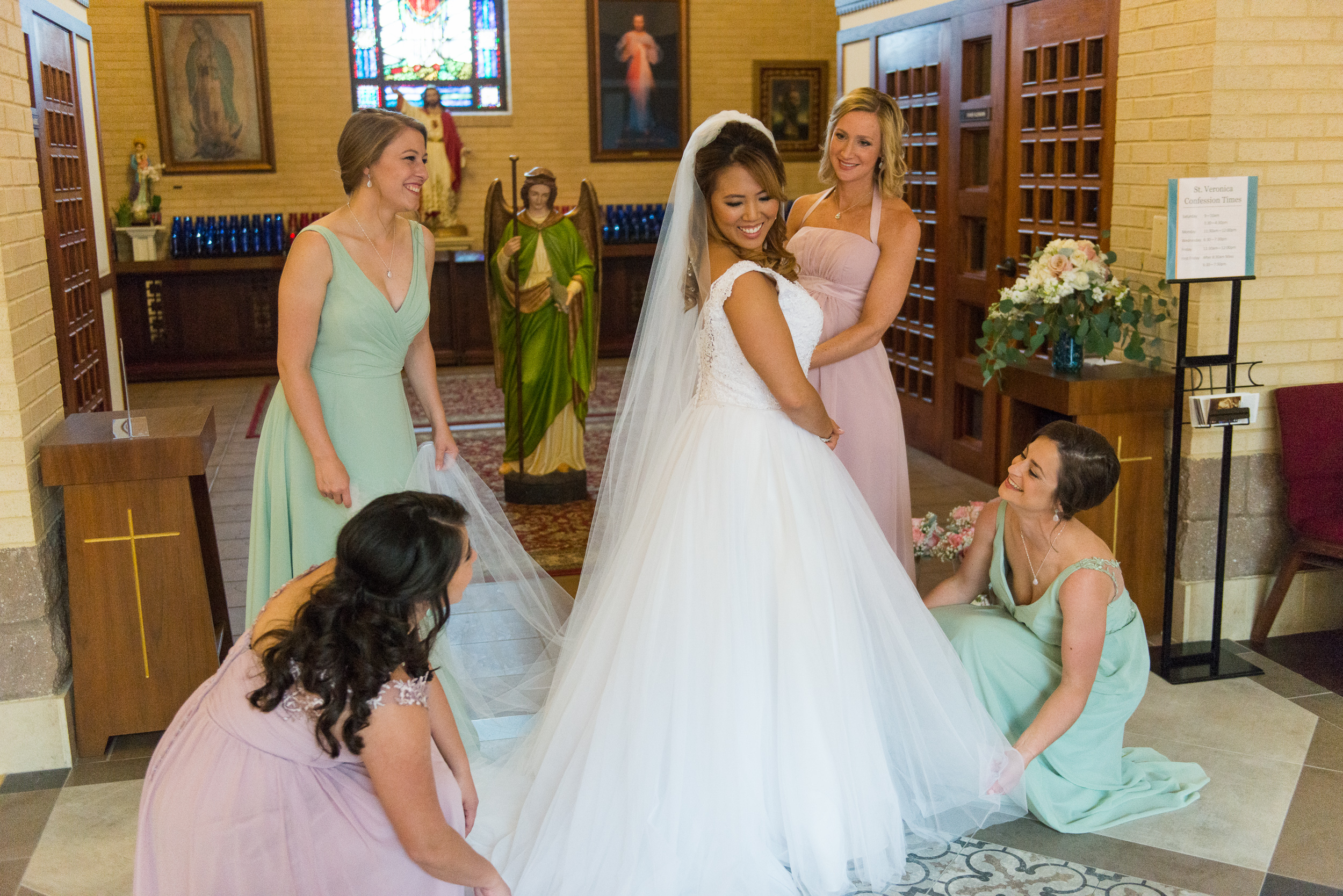 A bride surrounded by her bridesmaids before her wedding at St. Veronica Catholic Church in Chantilly, Virginia