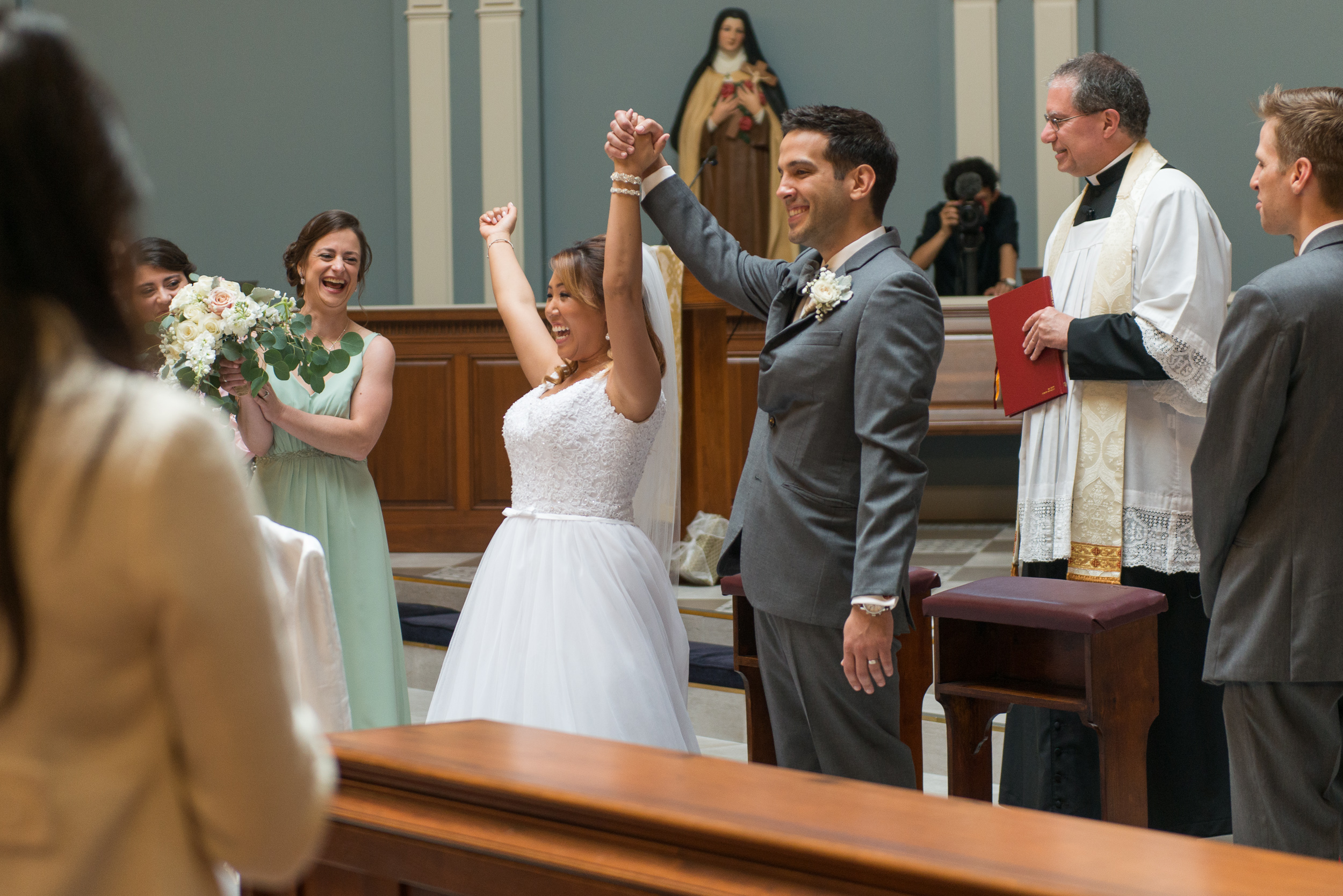 A bride and groom celebrate being announced husband and wife during their wedding ceremony at St. Veronica Catholic Church in Chantilly, Virginia