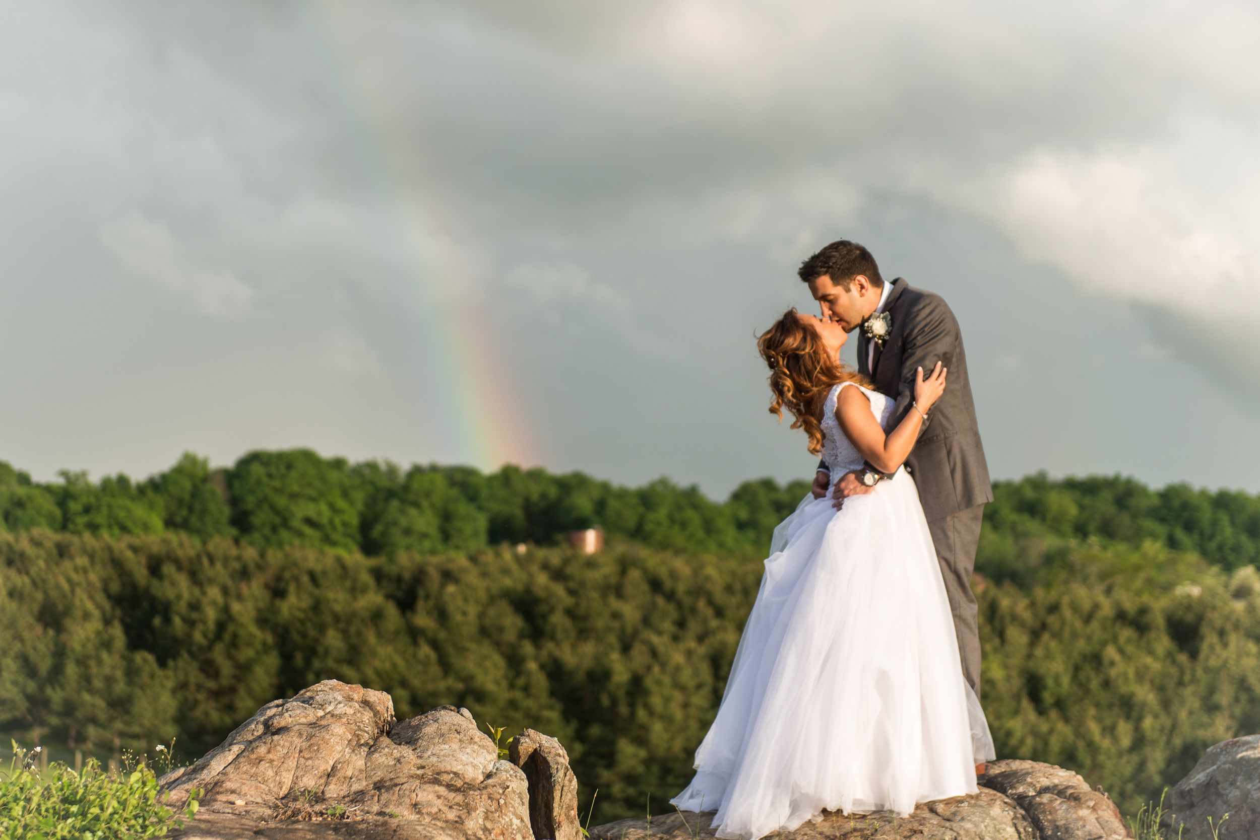 A bride and groom embrace and kiss with a rainbow in the background at Blue Valley Vineyard and Winery in Delaplane, Virginia