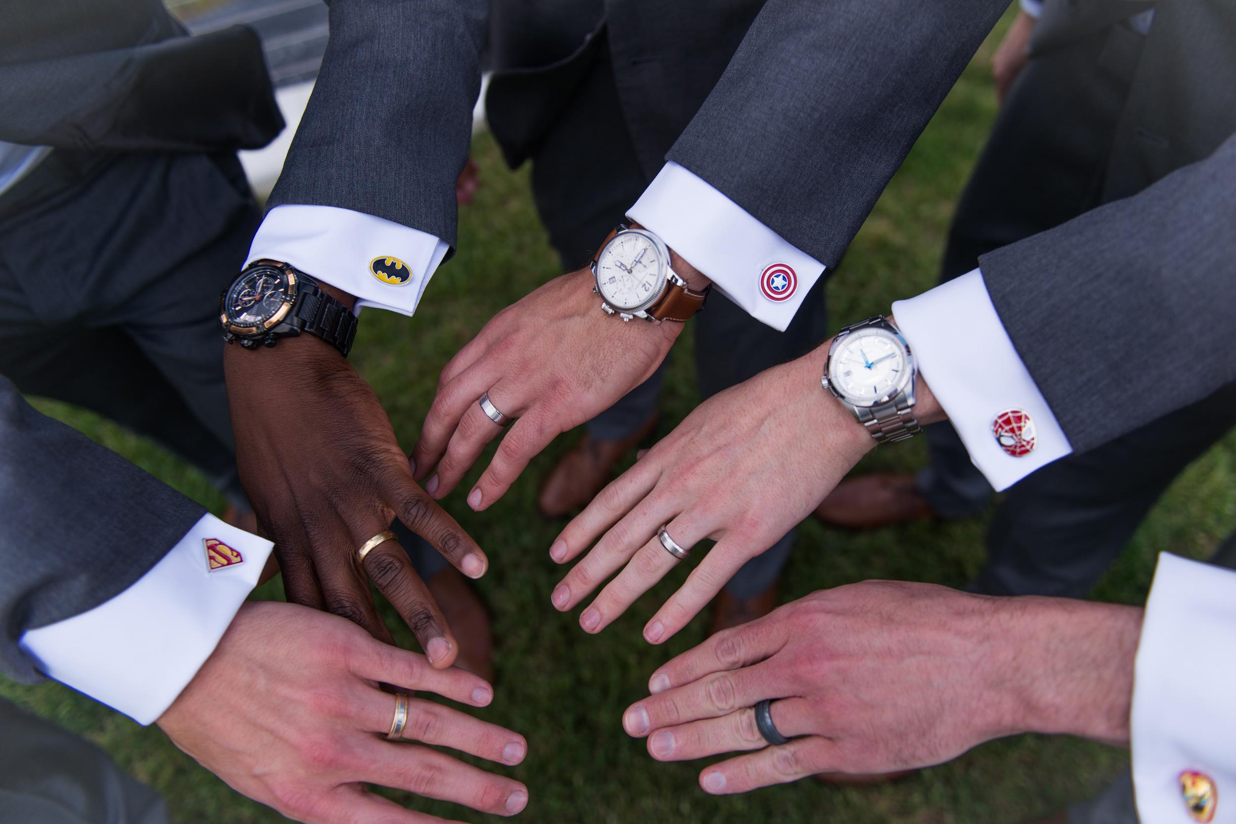 The groomsmen show off their superhero cufflinks and wedding rings during a wedding reception at Blue Valley Vineyard in Delaplane, Virginia