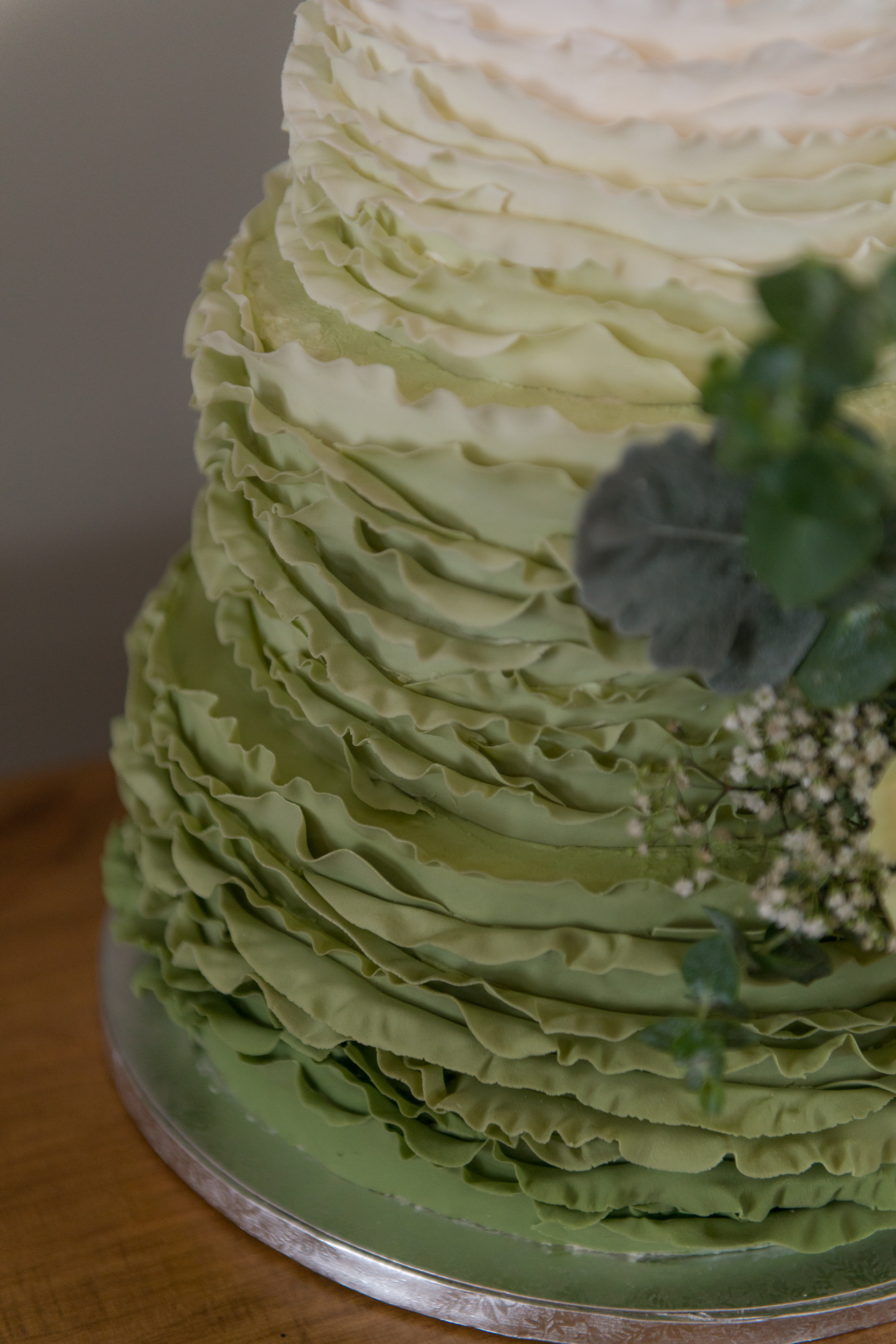 A wedding cake with green ruffle icing at a reception at Blue Valley Vineyard and Winery in Delaplane, Virginia
