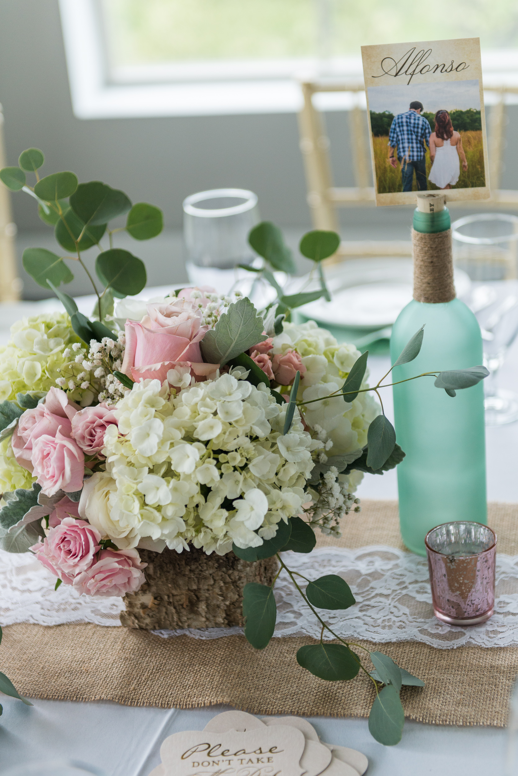 A table setting with a rustic pastel flower arrangement and wine bottle table numbers at a reception at Blue Valley Vineyard and Winery in Delaplane, Virginia