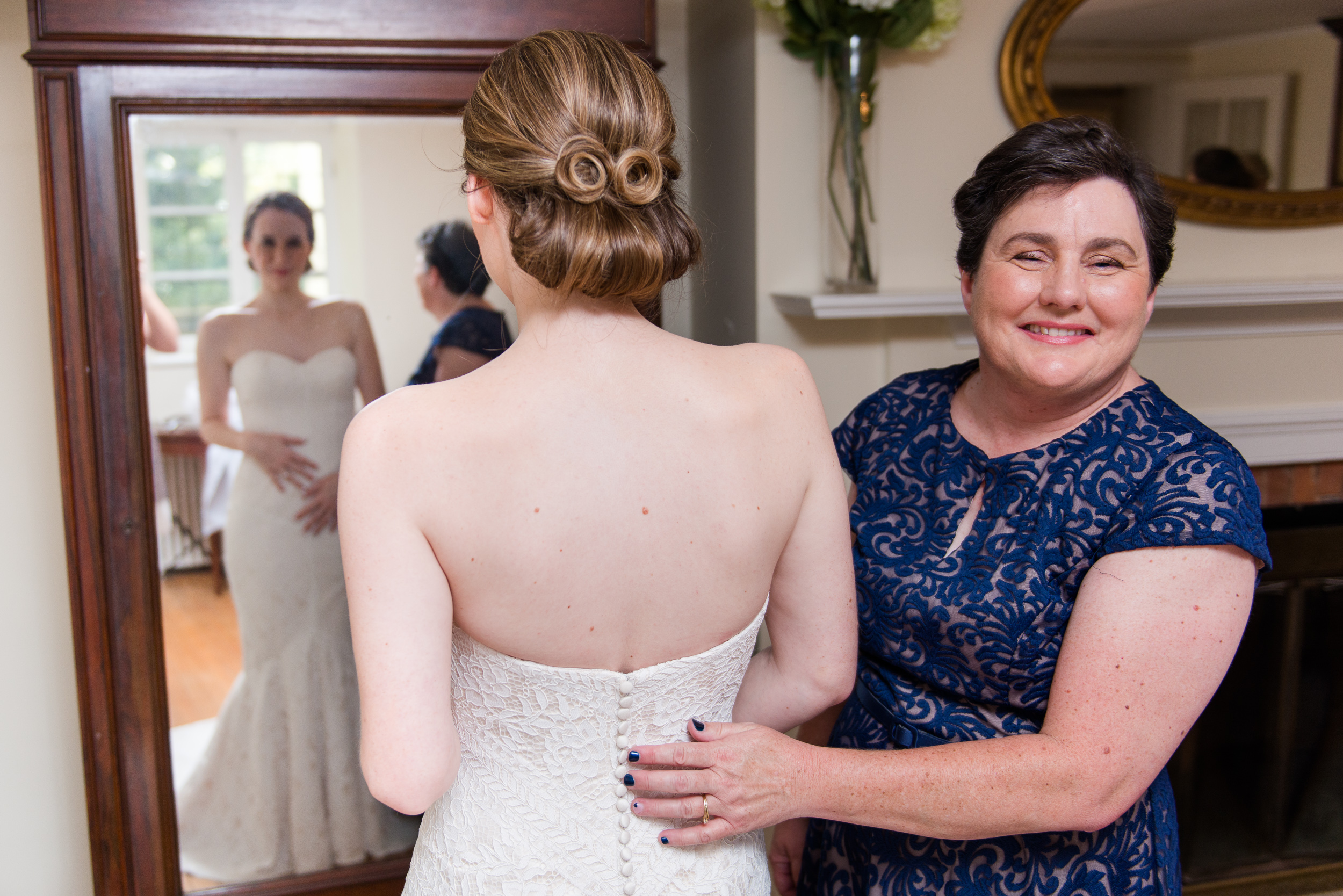 The mother of the bride smiles as she helps her daughter get ready before her wedding at Oatlands Historic House and Gardens in Leesburg, Virginia
