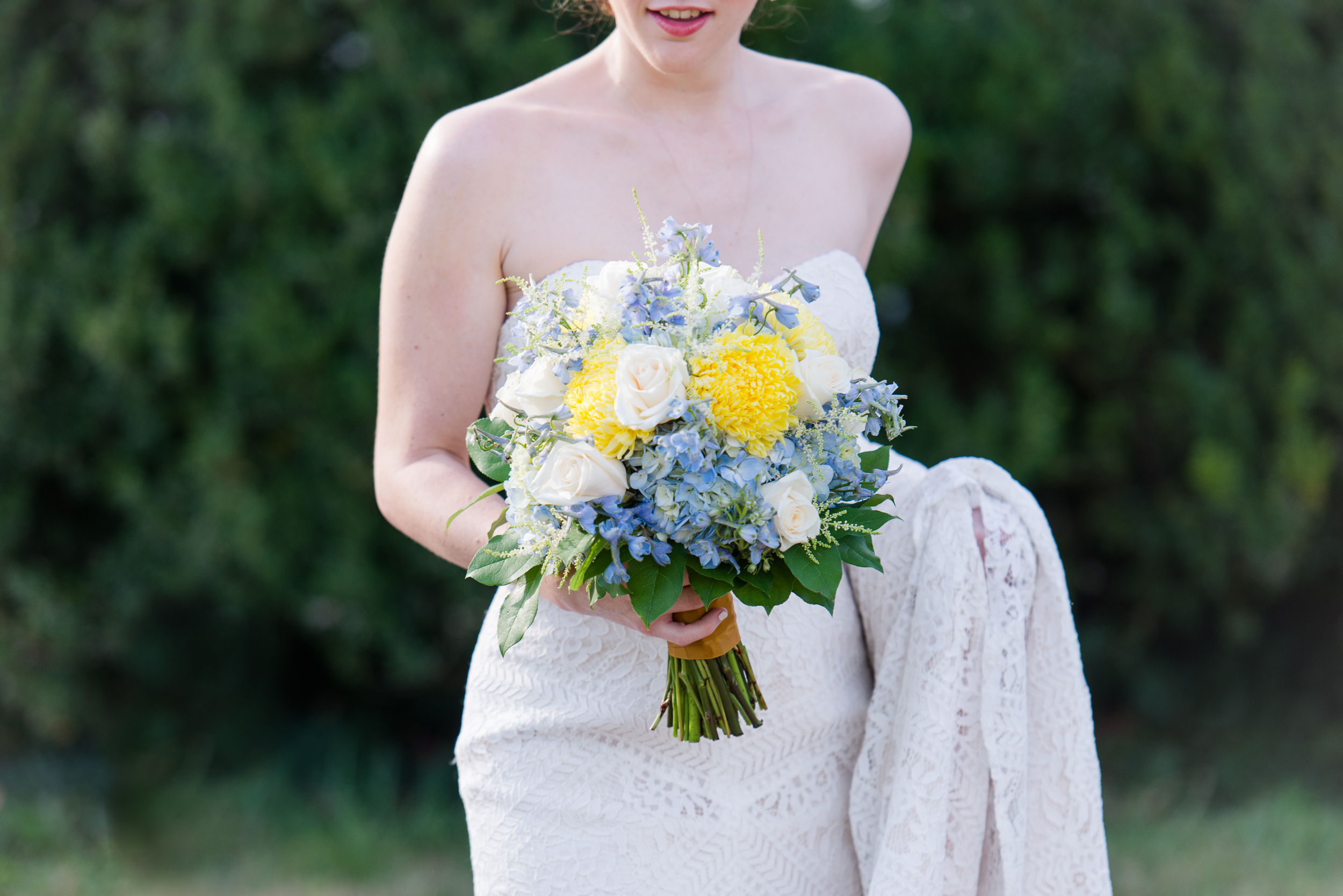 A bride holding the train of her romantic lace wedding dress and blue and yellow spring bouquet before her wedding at Oatlands Historic House and Gardens in Leesburg, Virginia