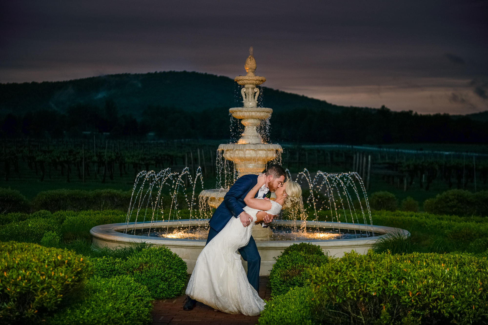 The bride and groom kiss outside the fountain at night outside Keswick Vineyards in Charlottesville, Virginia