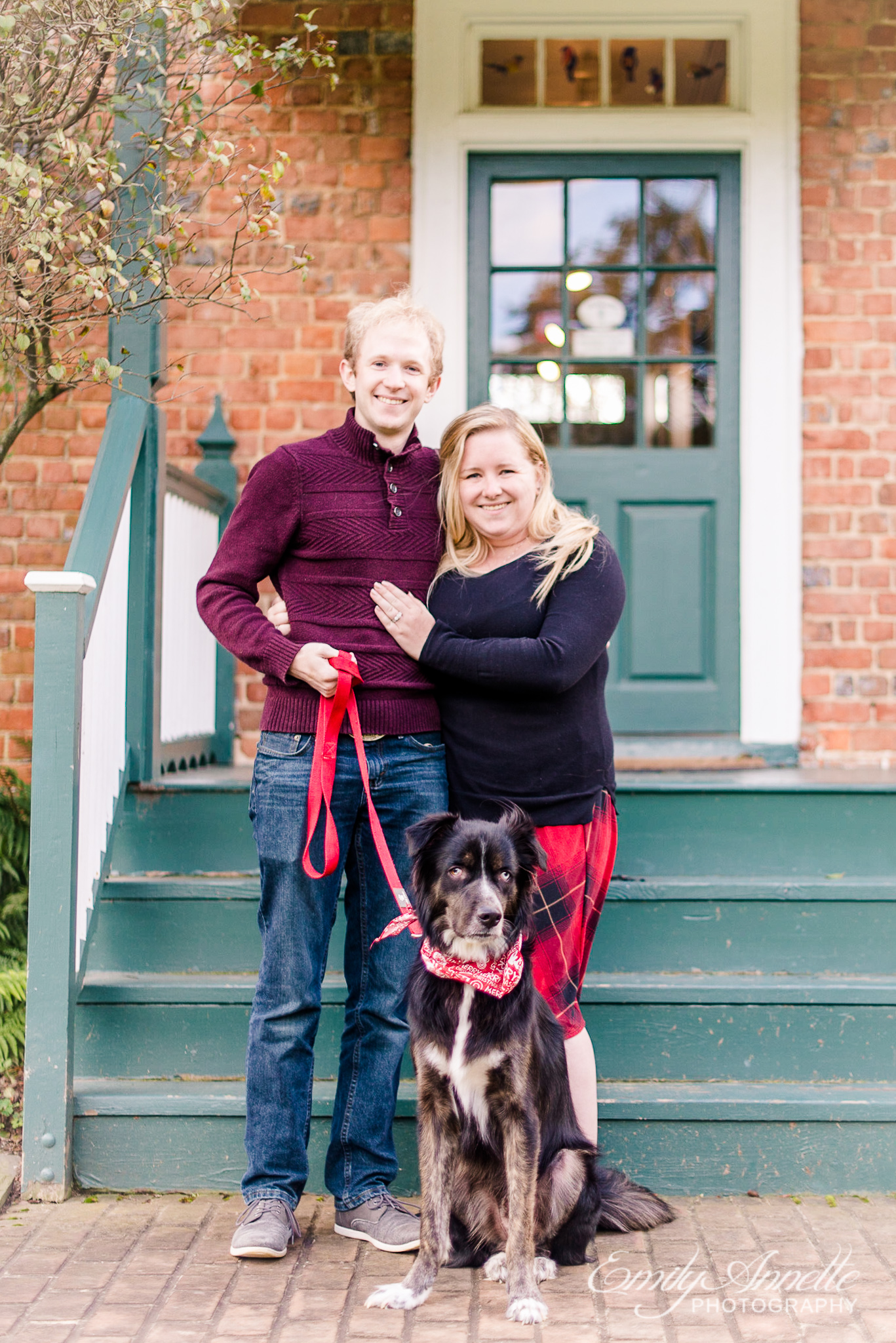 A couple pose with their dog in front of the historic house in the fall at Green Spring Gardens Park in Alexandria, Virginia