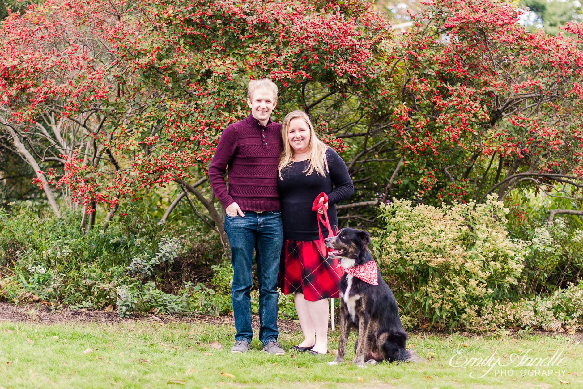 A couple pose with their dog in front of the gardens in the fall at Green Spring Gardens Park in Alexandria, Virginia