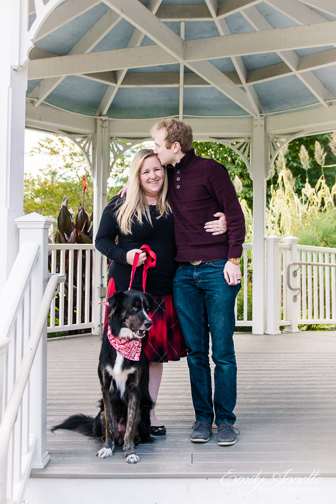 A couple pose with their dog under a gazebo in the fall at Green Spring Gardens Park in Alexandria, Virginia