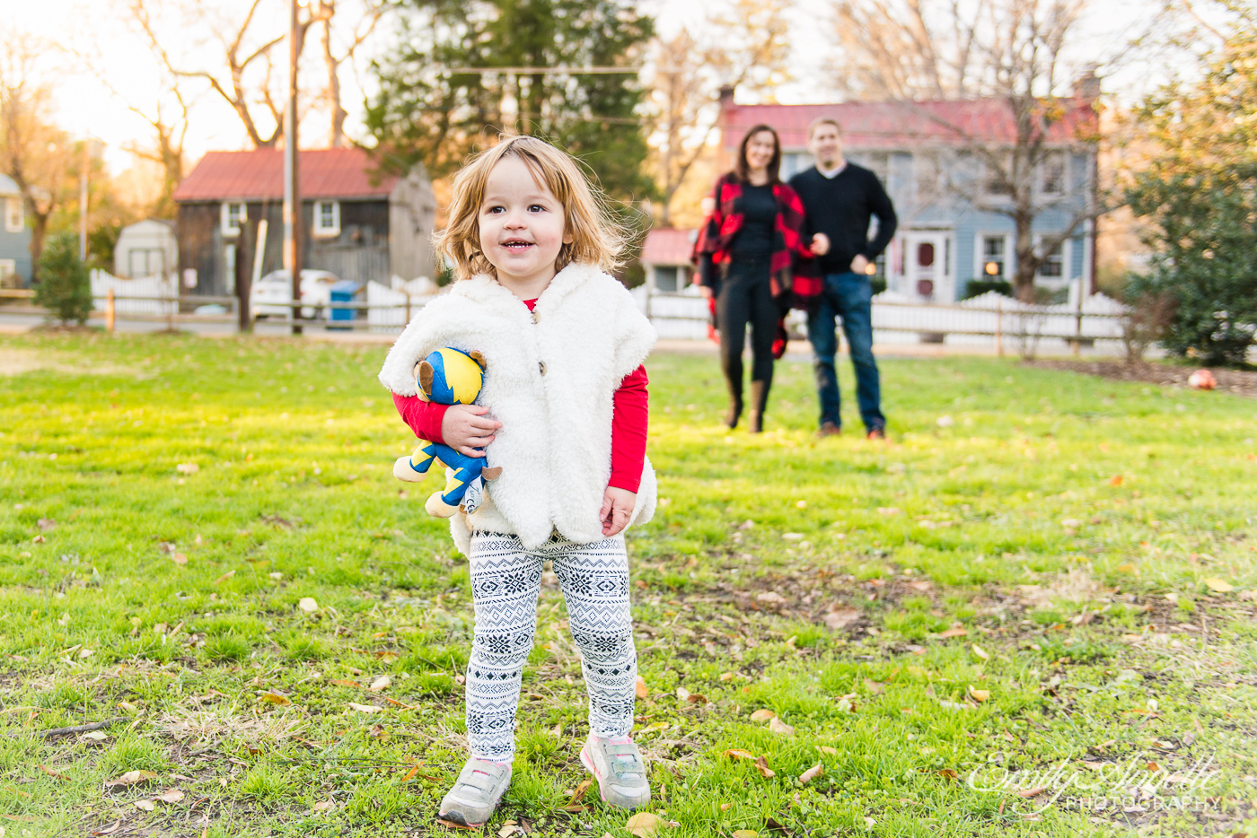 A young girl smiling for the camera in front of her parents for family photos at Clifton Town Park in Fairfax County, Virginia