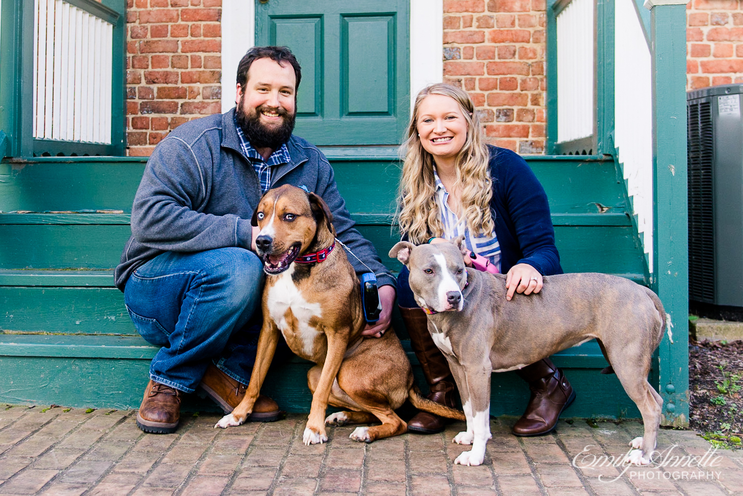 A couple posing together with their two dogs in front of the historic house at Green Spring Gardens Park in Fairfax, Virginia