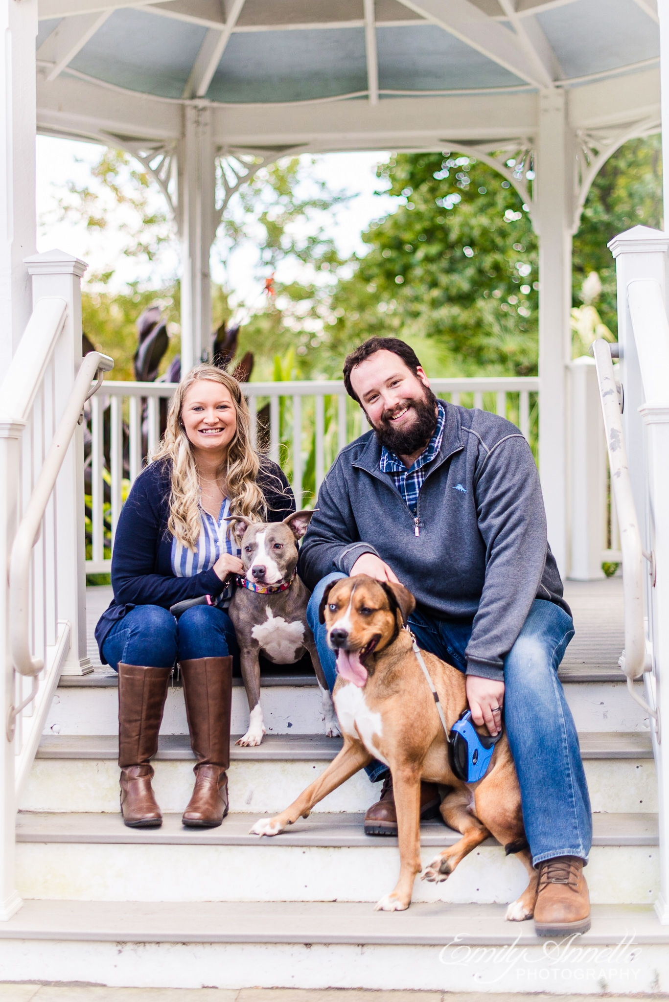 A couple posing together on the stairs to a gazebo while holding their two dogs in the garden at Green Spring Gardens Park in Fairfax, Virginia