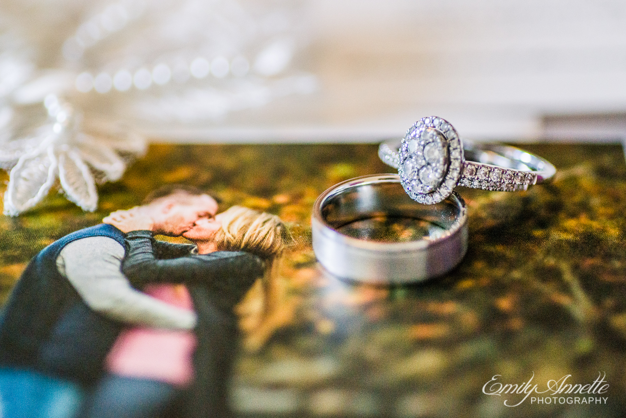 A diamond and silver wedding ring set next to a photo of the couple kissing at Herrington on the Bay in North Beach, Maryland
