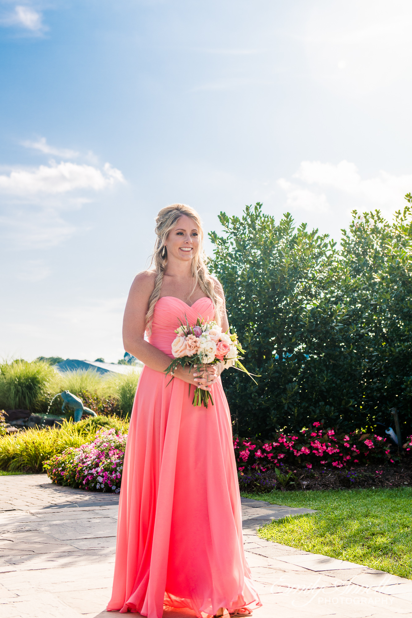 A bridesmaid begins walking down the aisle holding a tropical flower bouquet and wearing a coral colored maxi dress during a wedding at Herrington on the Bay in North Beach, Maryland