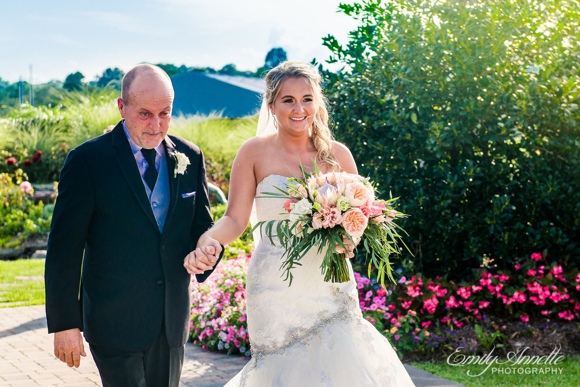 A bride walks down the aisle with her father while she holds a big tropical flower bouquet during a wedding at Herrington on the Bay in North Beach, Maryland