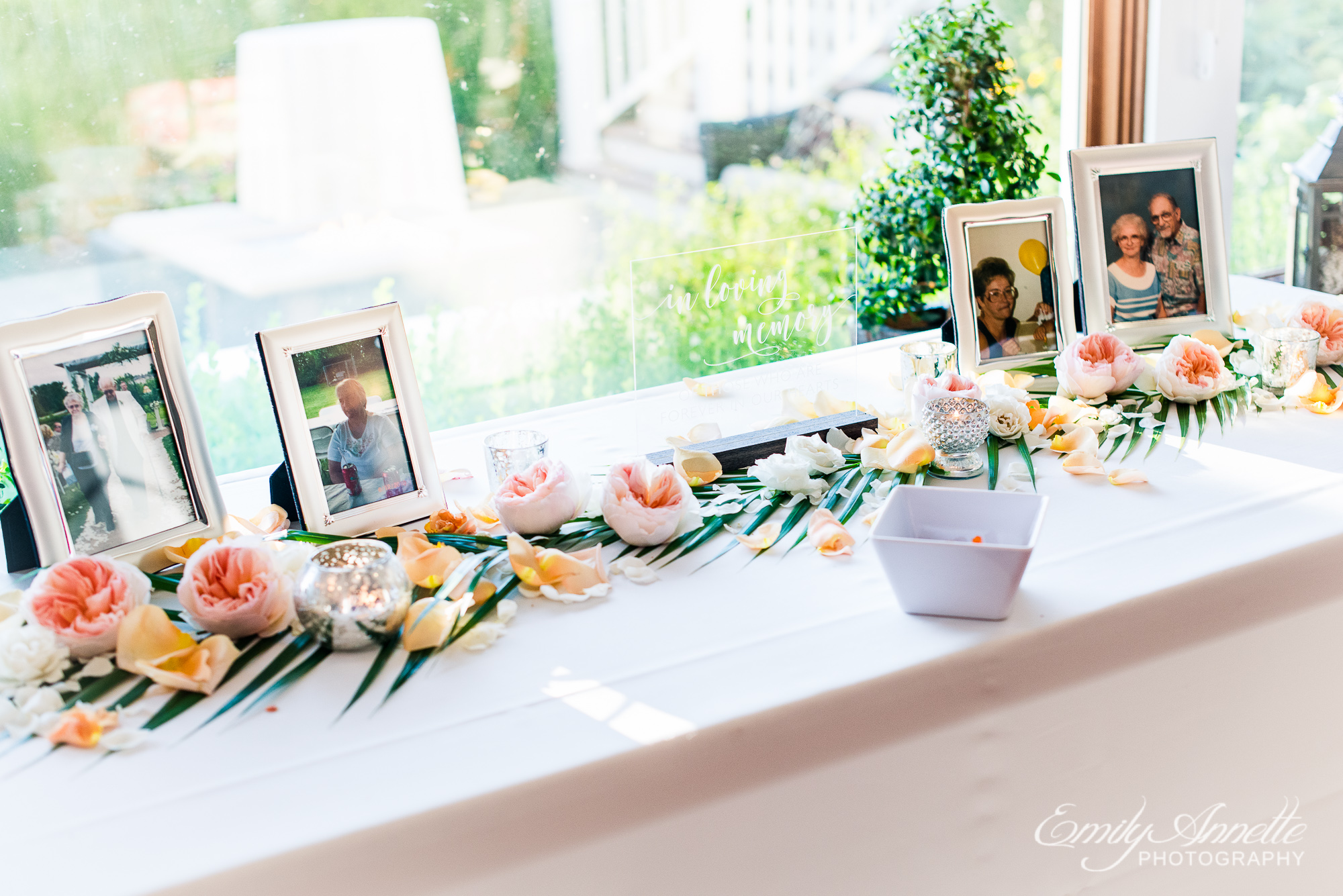 A table set with tropical flowers and framed photos of deceased loved ones at a wedding reception at Herrington on the Bay in North Beach, Maryland