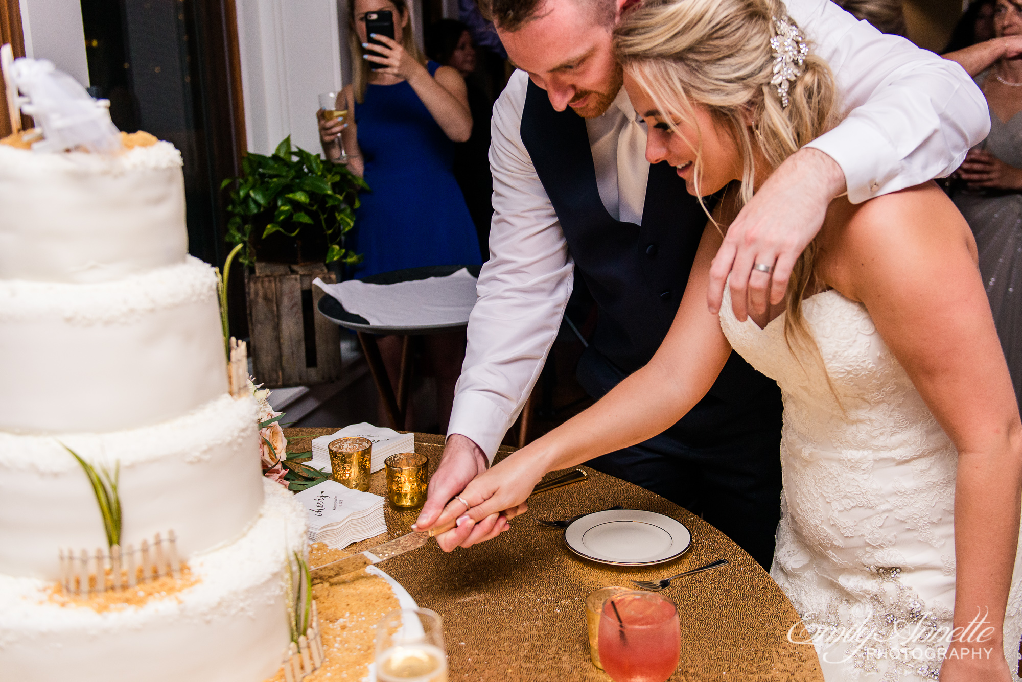 A bride and groom cut their wedding cake during their reception at Herrington on the Bay in North Beach, Maryland