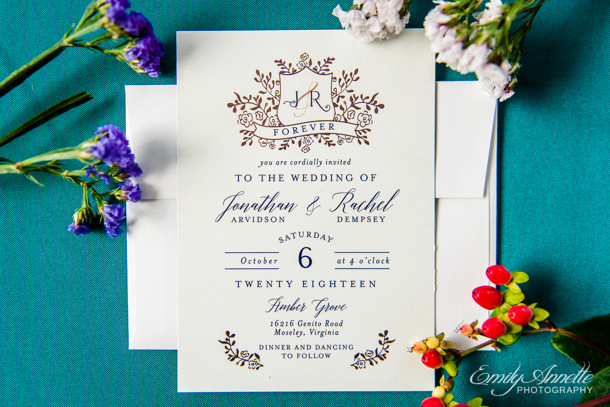 A flatlay with a classic romantic rose gold wedding invitation with small flowers on a blue background for a wedding at Amber Grove near Richmond, Virginia