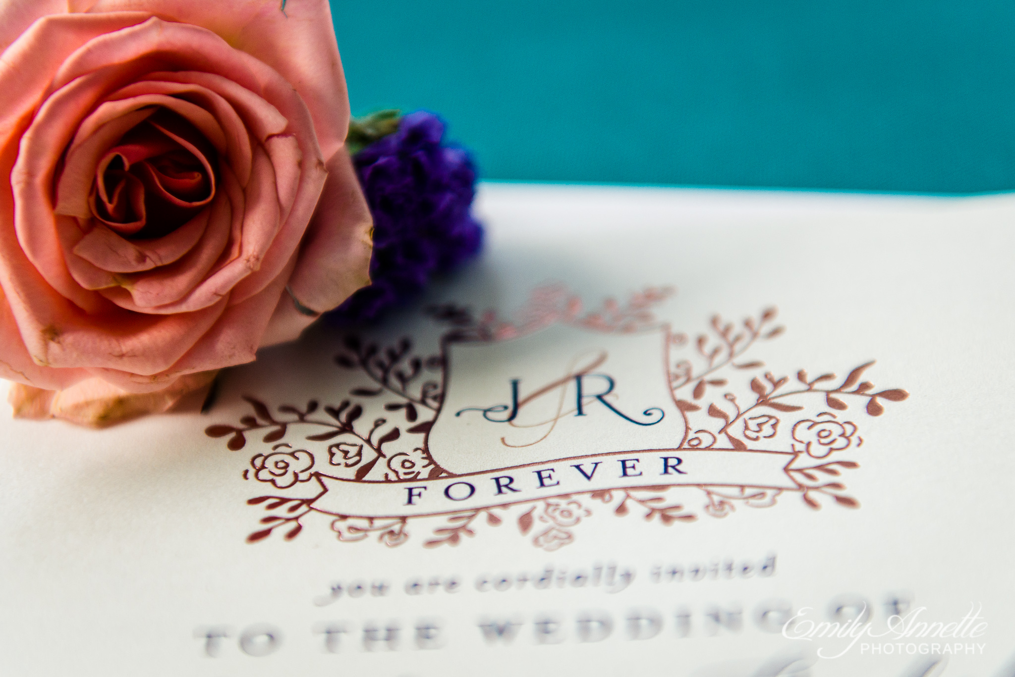 A pink rose sitting on a rose gold wedding invitation monogram for a wedding at Amber Grove near Richmond, Virginia