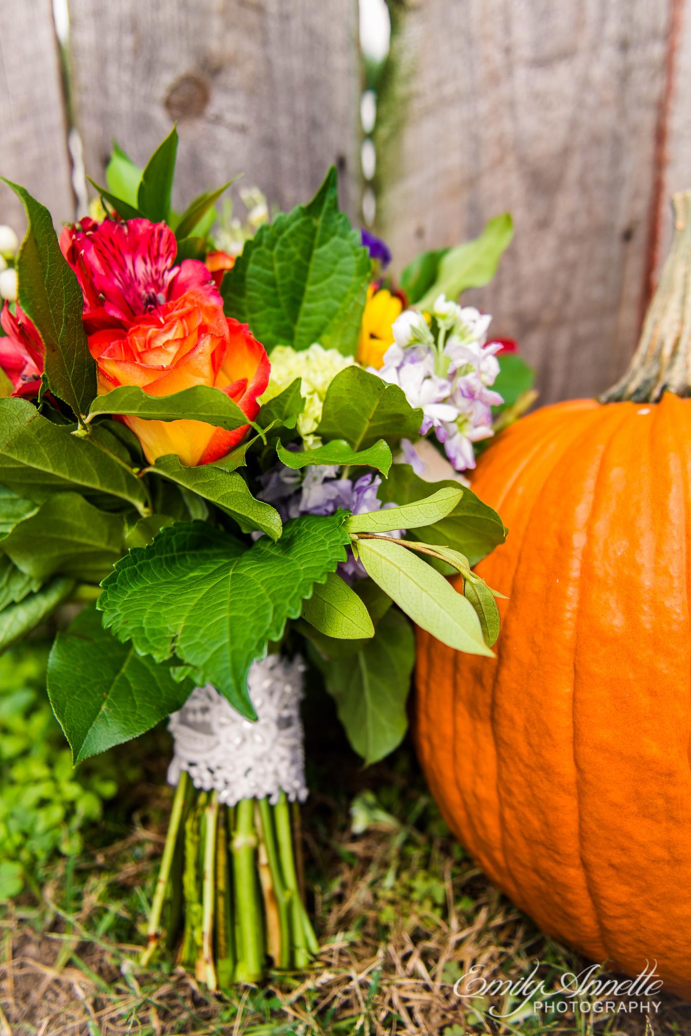 A fall bridal bouquet next to a pumpkin before a wedding at Amber Grove near Richmond, Virginia