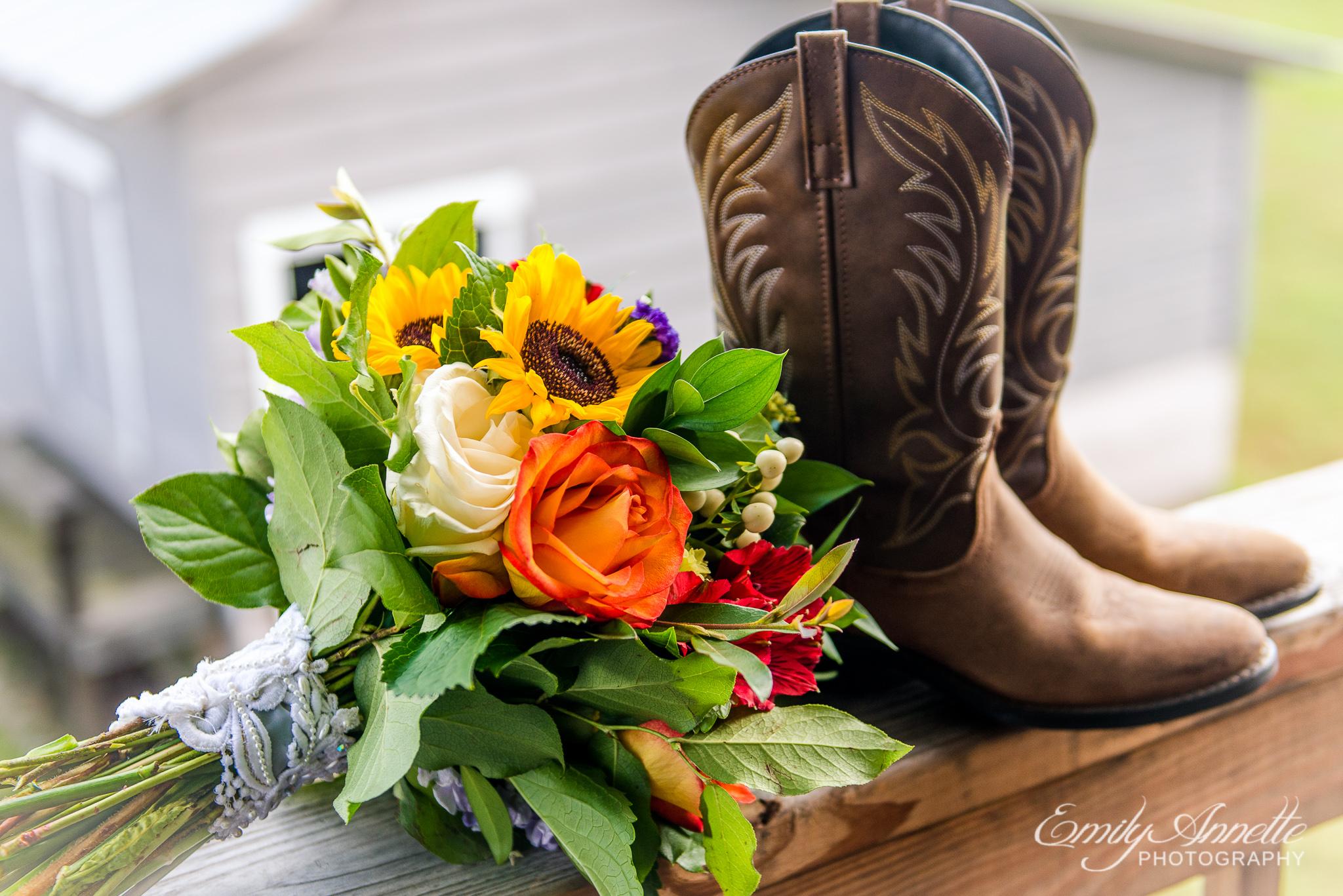 A fall bridal bouquet lies next to a pair of cowboy boots before a wedding at Amber Grove near Richmond, Virginia