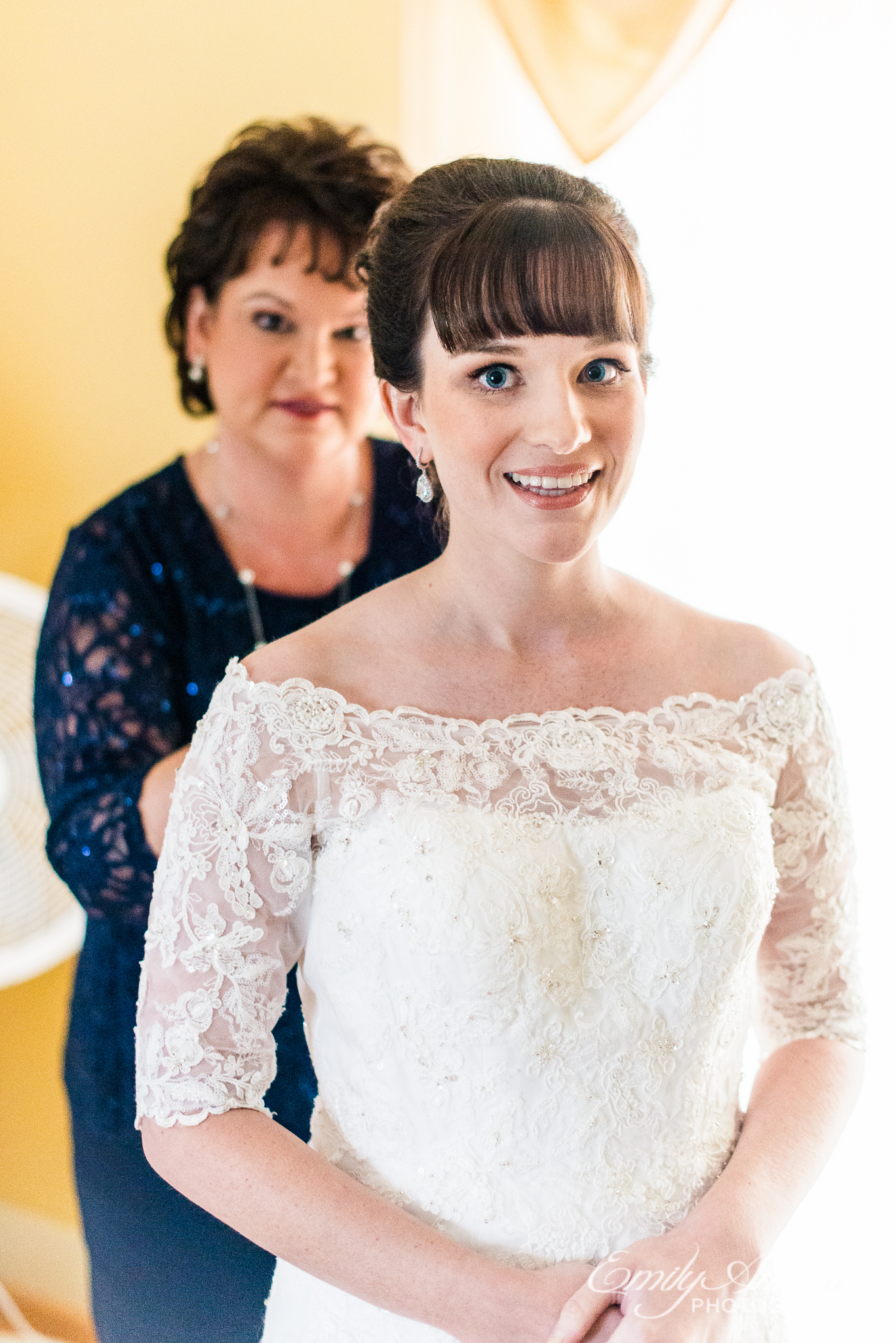 A bride smiles at the camera while the mother of the bride helps her get dressed before her wedding ceremony at Amber Grove near Richmond, Virginia