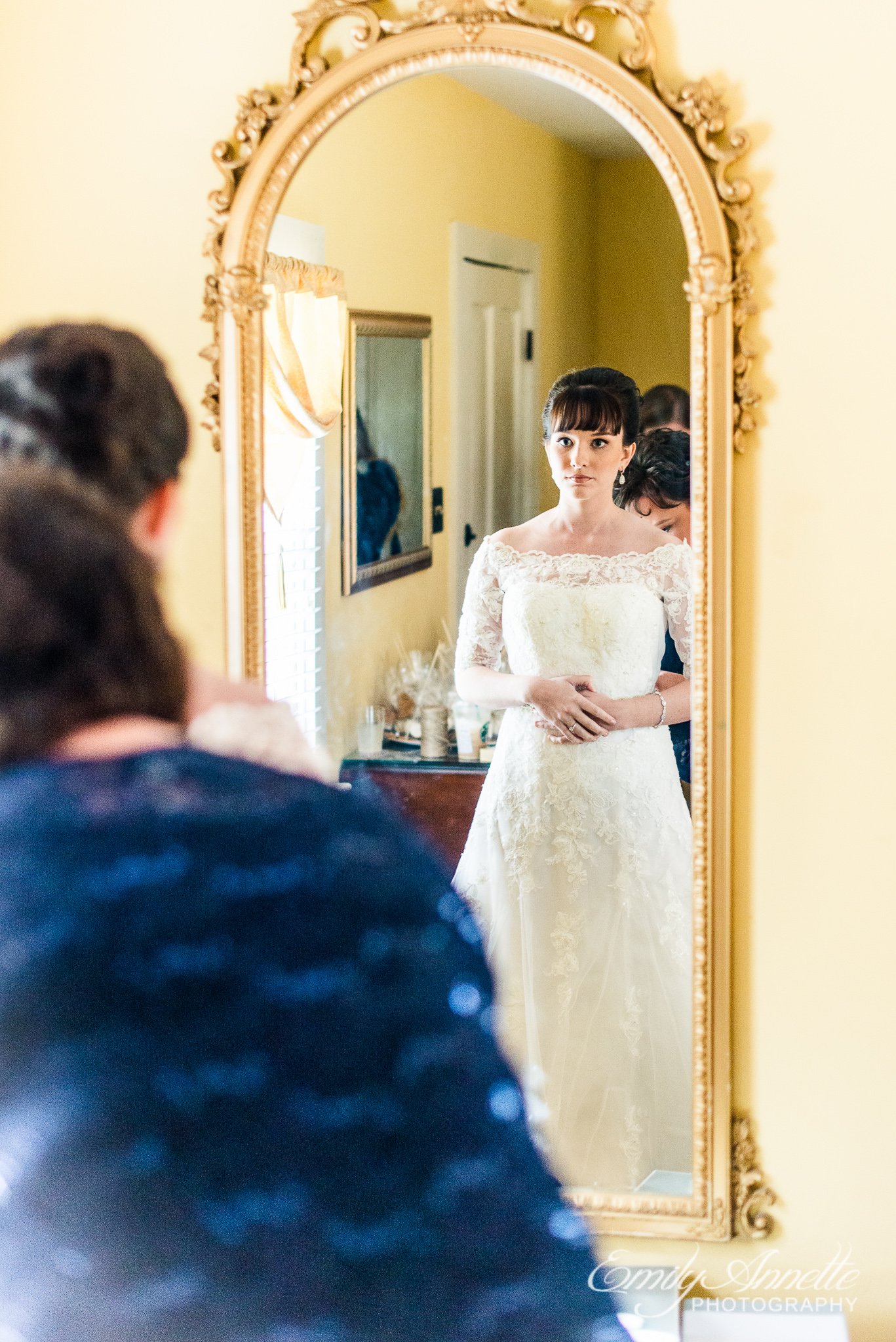 A bride looks through the mirror while the mother of the bride helps her daughter get dressed before her wedding ceremony at Amber Grove near Richmond, Virginia