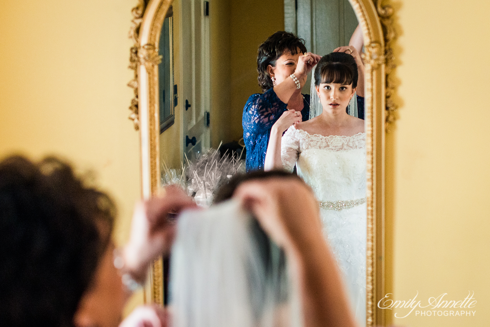 A bride looks through the mirror while the mother of the bride helps her put on her veil while getting ready before her wedding ceremony at Amber Grove near Richmond, Virginia