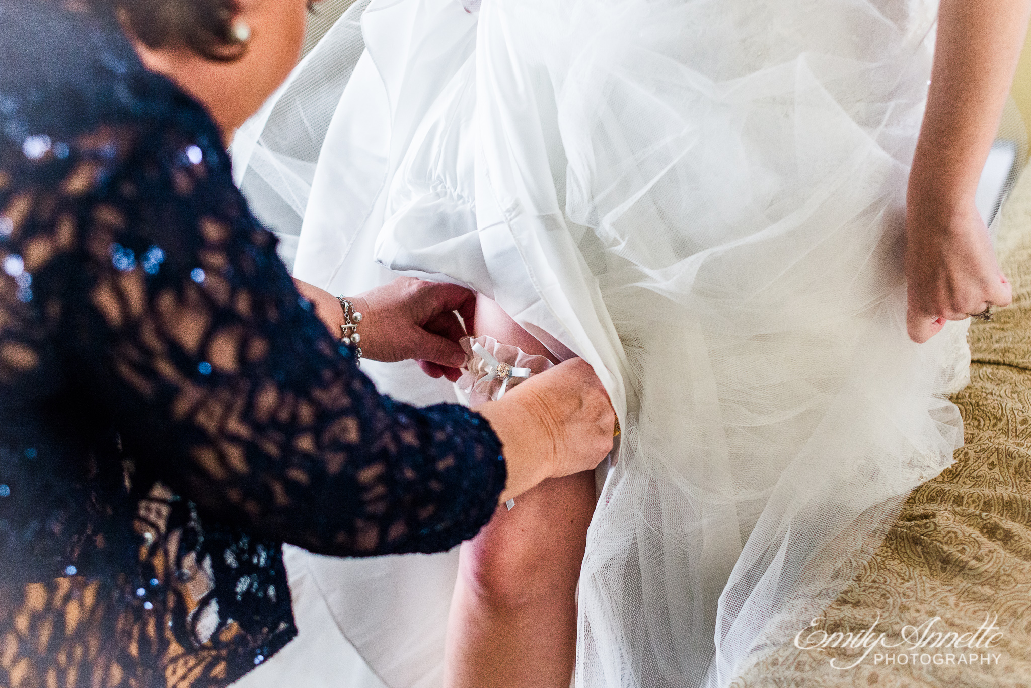 The mother of the bride helps her put on her garter before her wedding ceremony at Amber Grove near Richmond, Virginia