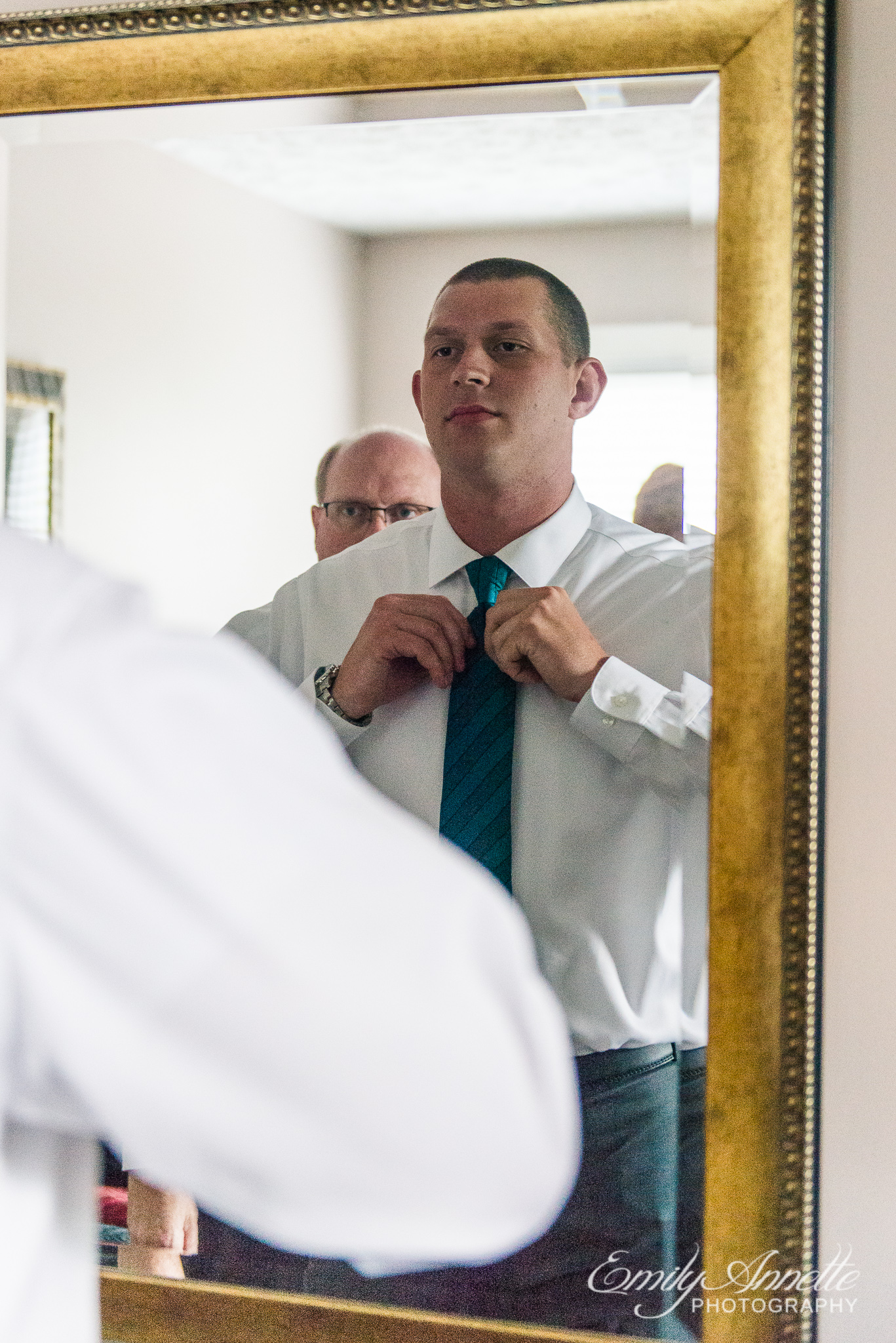 A groom looks through a mirror and adjusts his tie while getting ready before his wedding ceremony at Amber Grove near Richmond, Virginia