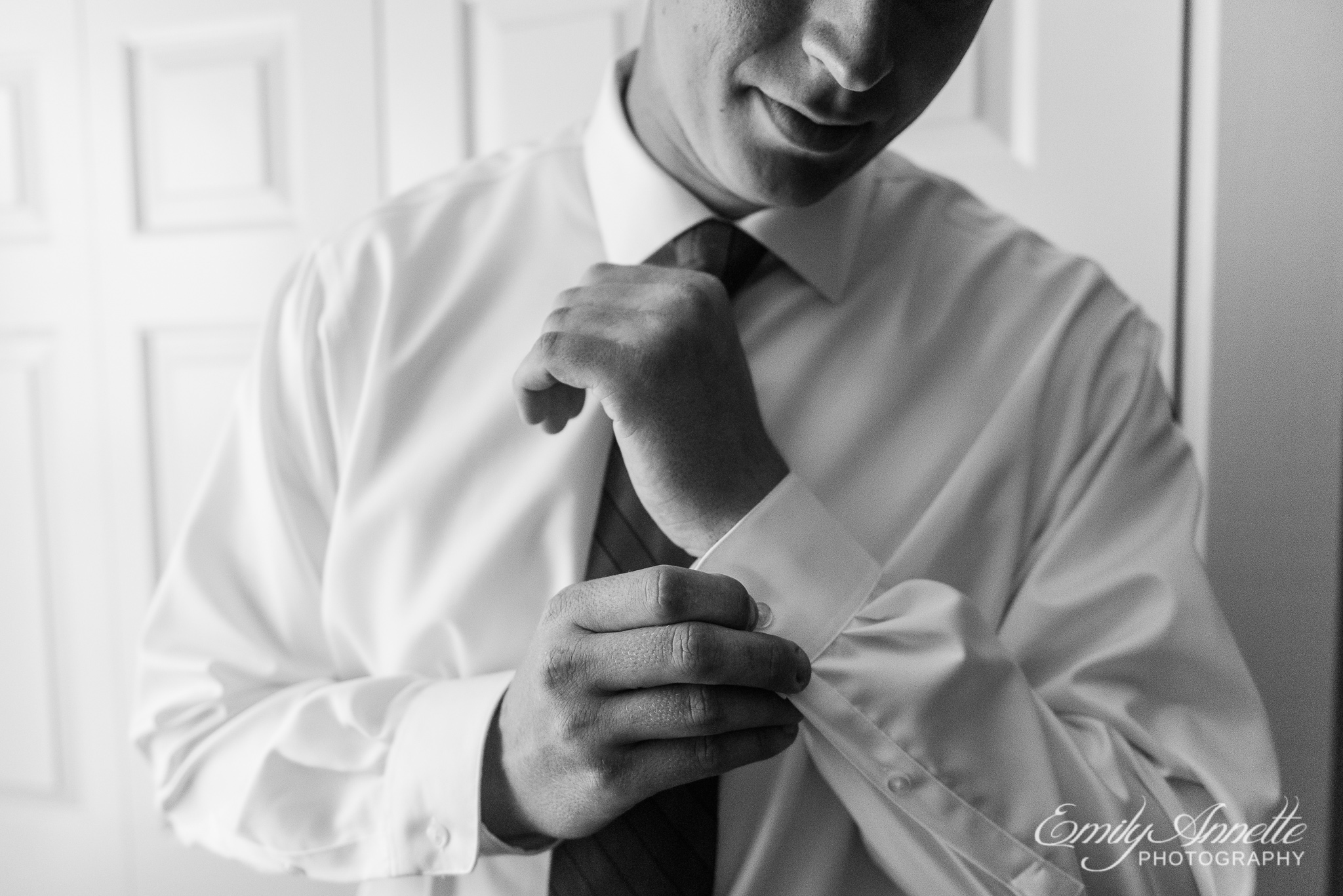A groom adjusts his cuffs while getting ready before his wedding ceremony at Amber Grove near Richmond, Virginia