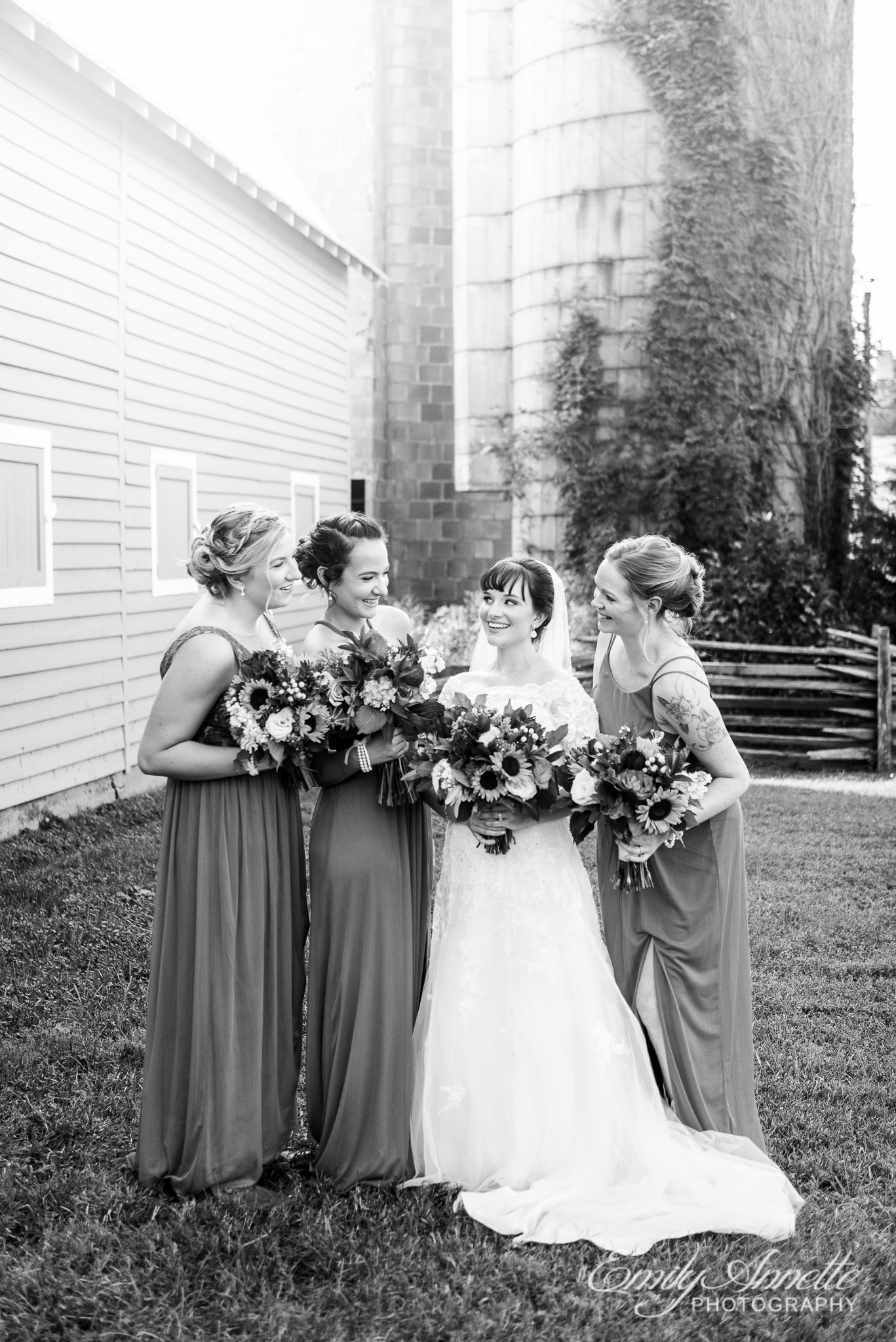 A bridal party poses for a photo in blue bridesmaids dresses and holding colorful fall bouquets outside a silo during a country wedding at Amber Grove near Richmond, Virginia