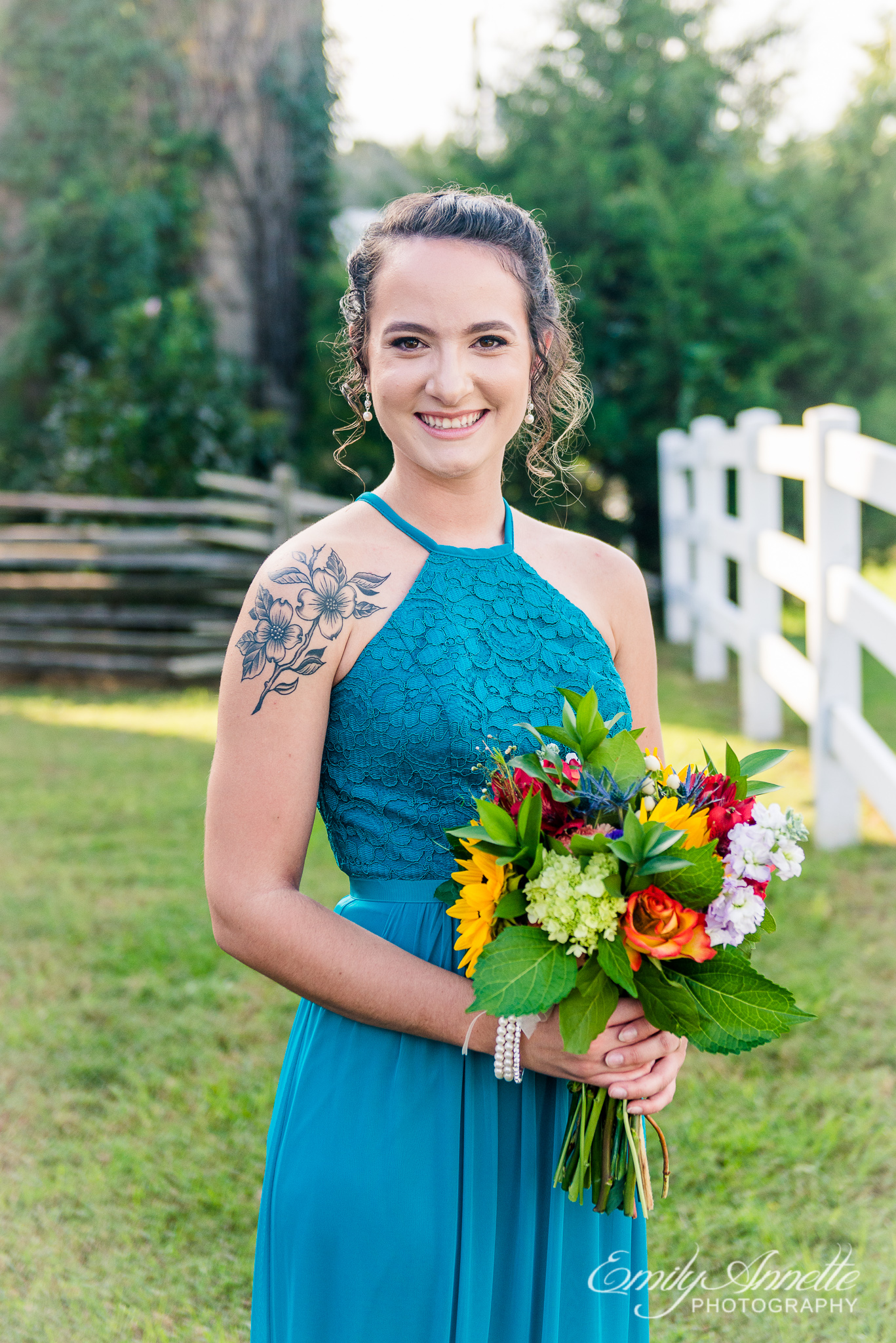 A bridesmaid poses for a portrait in a blue maxi dress holding a colorful bouquet outside a silo during a country wedding at Amber Grove near Richmond, Virginia