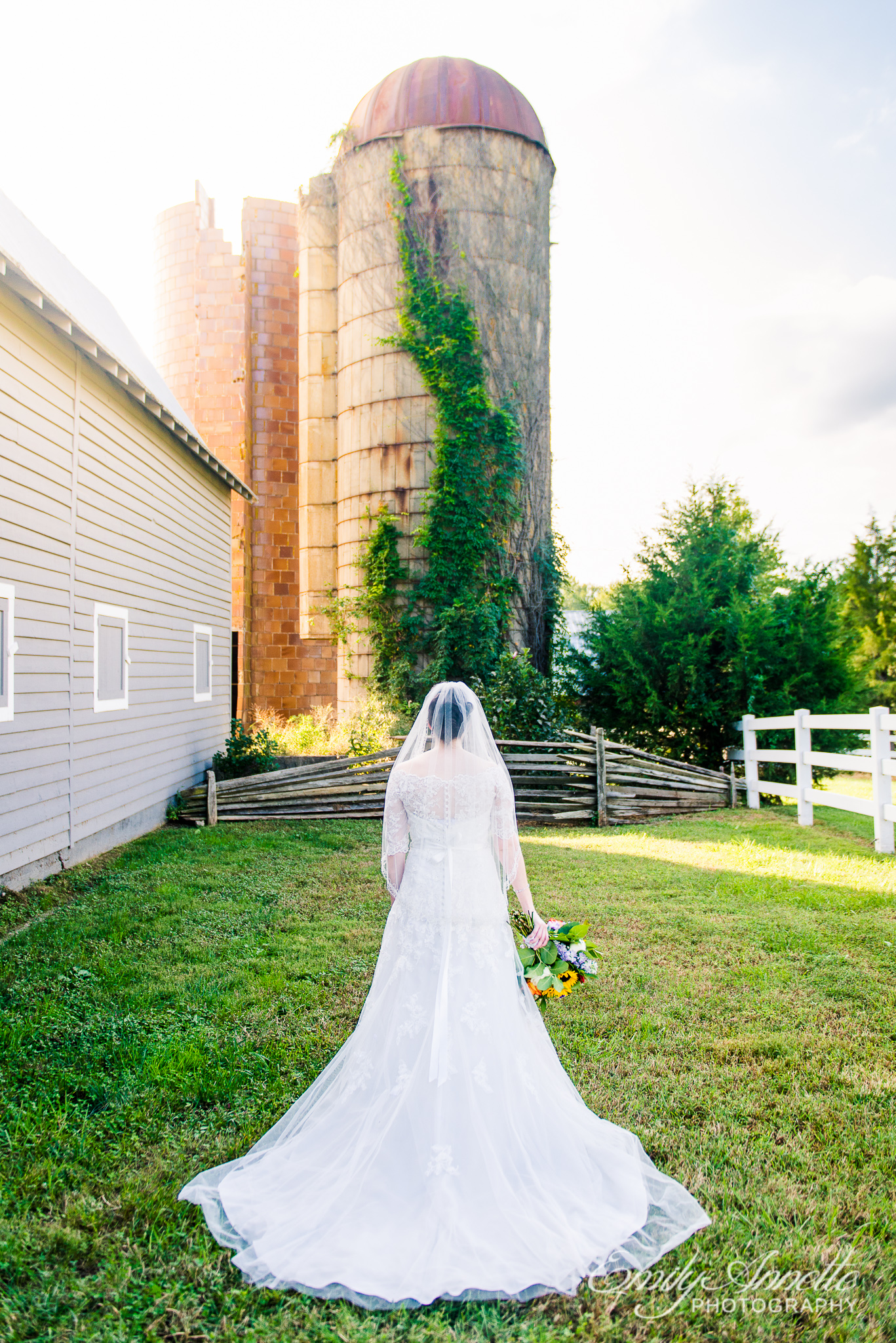 A bride poses for a portrait showing the back of her dress with a chapel train holding a colorful bouquet outside a silo during a country wedding at Amber Grove near Richmond, Virginia