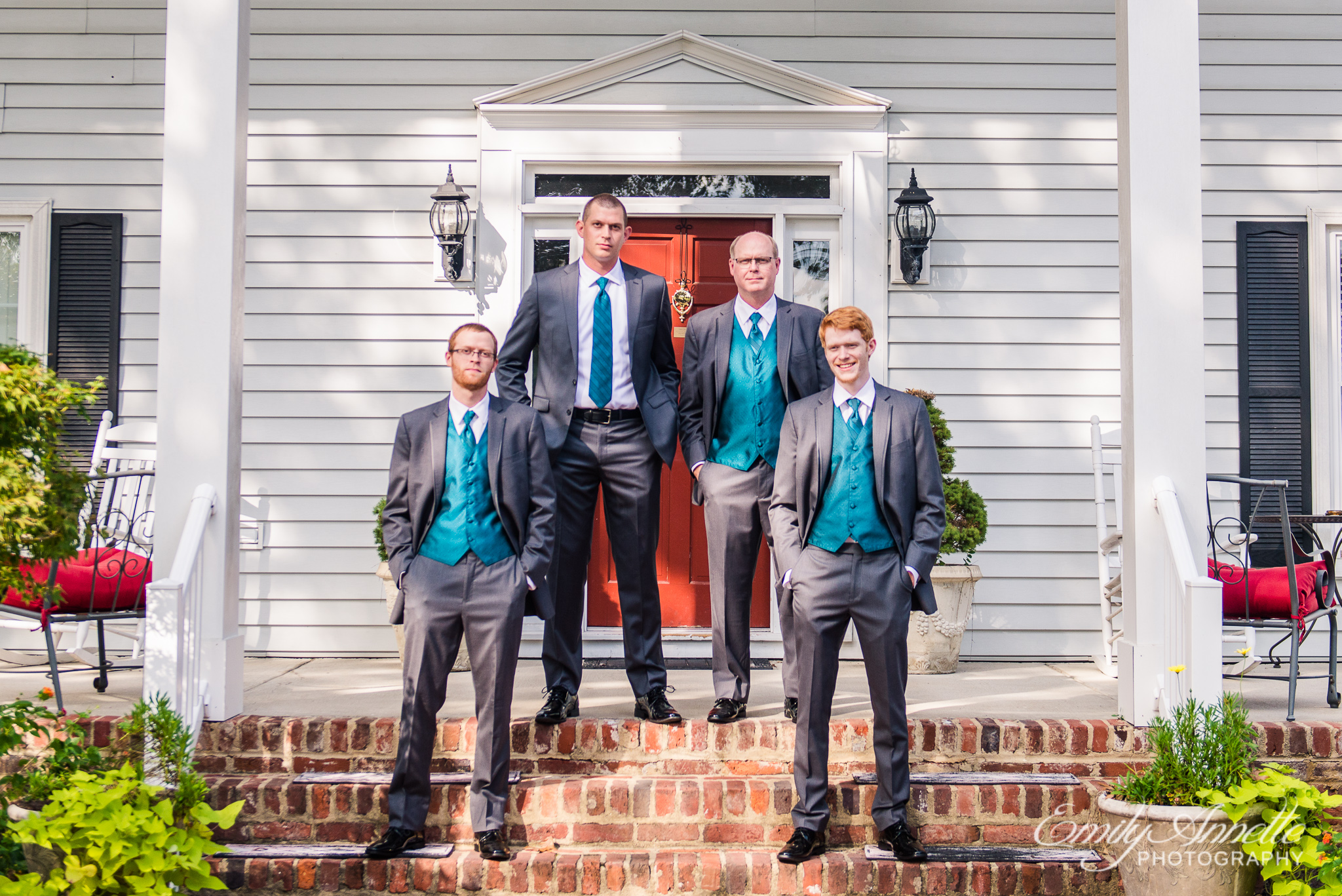 A groom and his groomsmen pose on the front porch of a historic house during a country wedding at Amber Grove near Richmond, Virginia