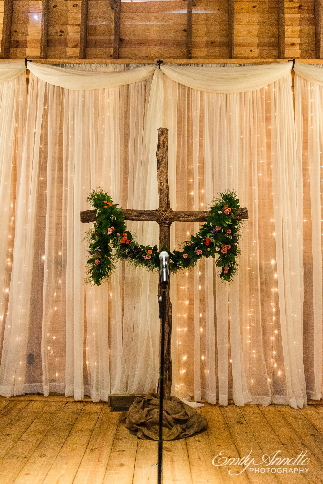 A wooden cross decorated with a garland of colorful flowers and greenery for a wedding ceremony during a country wedding at Amber Grove near Richmond, Virginia