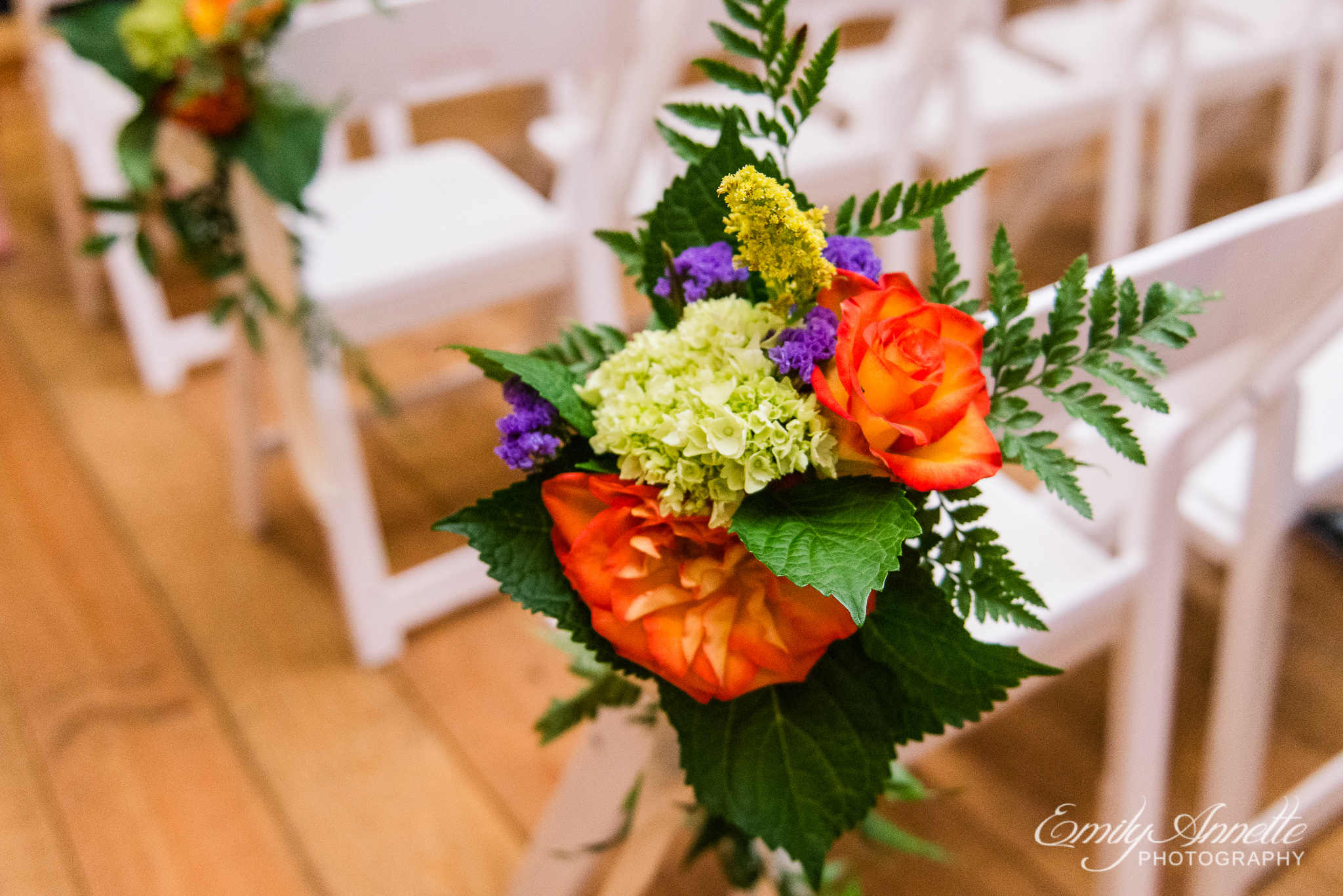 Fall flowers decorating the end of a row of chairs inside the wedding site during a country wedding at Amber Grove near Richmond, Virginia