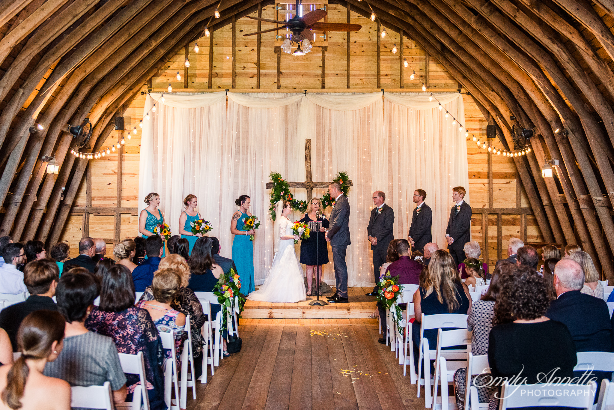 A bride and groom stand with the wedding party and an officiant inside a decorated barn for a wedding ceremony during a country wedding at Amber Grove near Richmond, Virginia