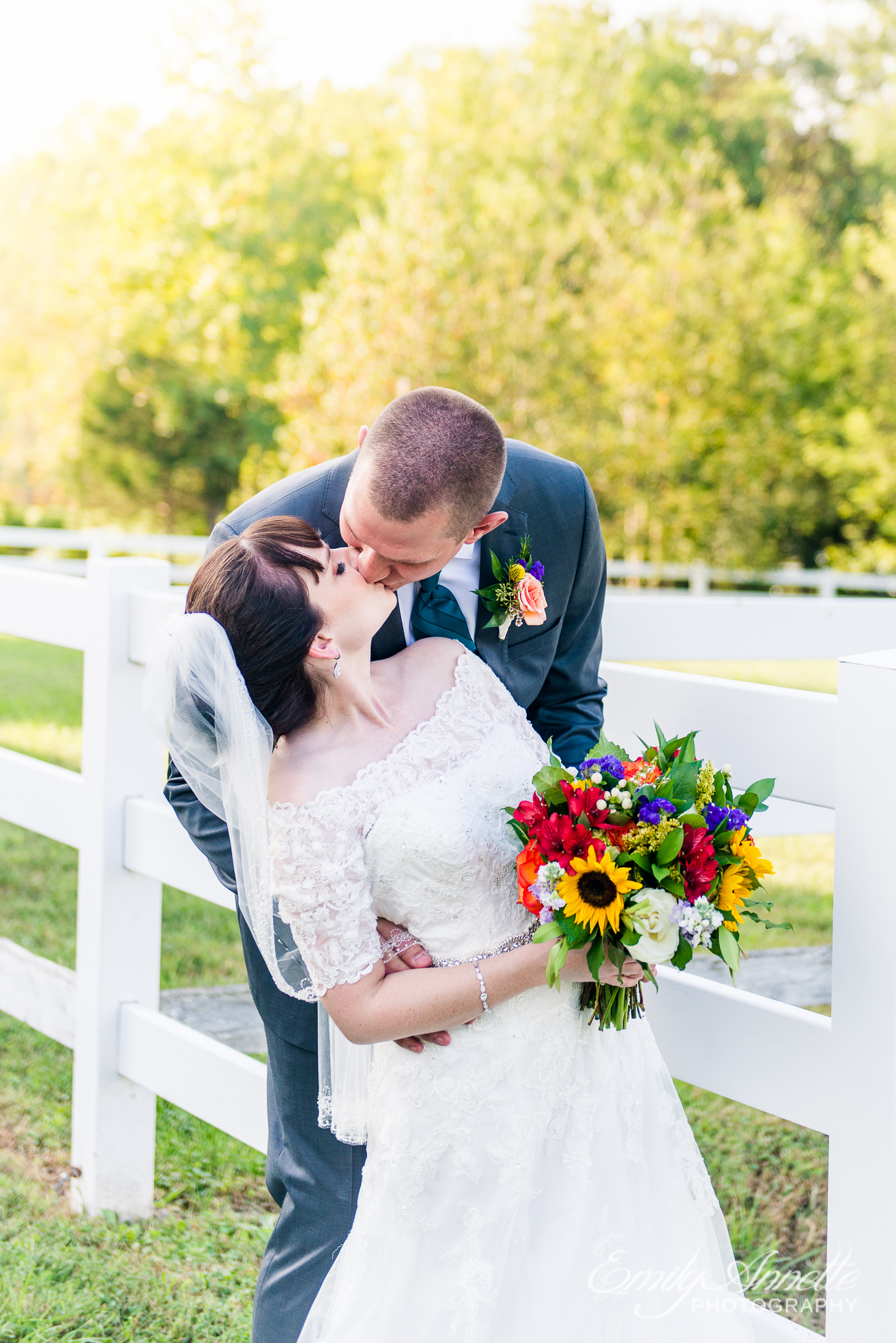 A bride and groom share a kiss next to a white fence during a country wedding at Amber Grove near Richmond, Virginia