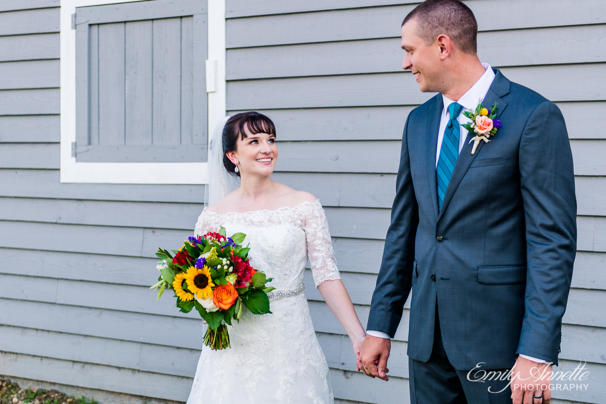A bride and groom hold hands and smile at each other after their country wedding at Amber Grove near Richmond, Virginia