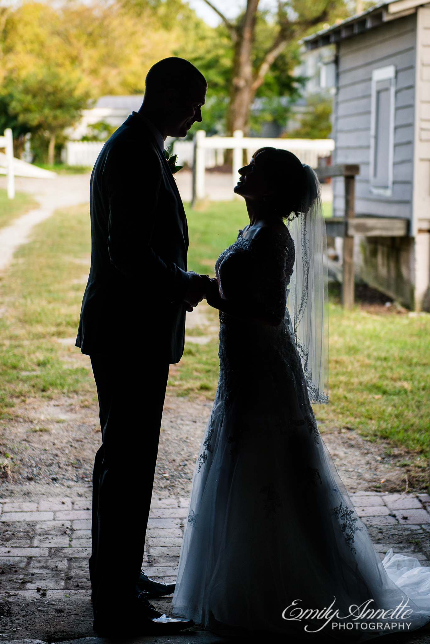 A silhouette of a bride and groom holding hands and looking at each other during their country wedding at Amber Grove near Richmond, Virginia