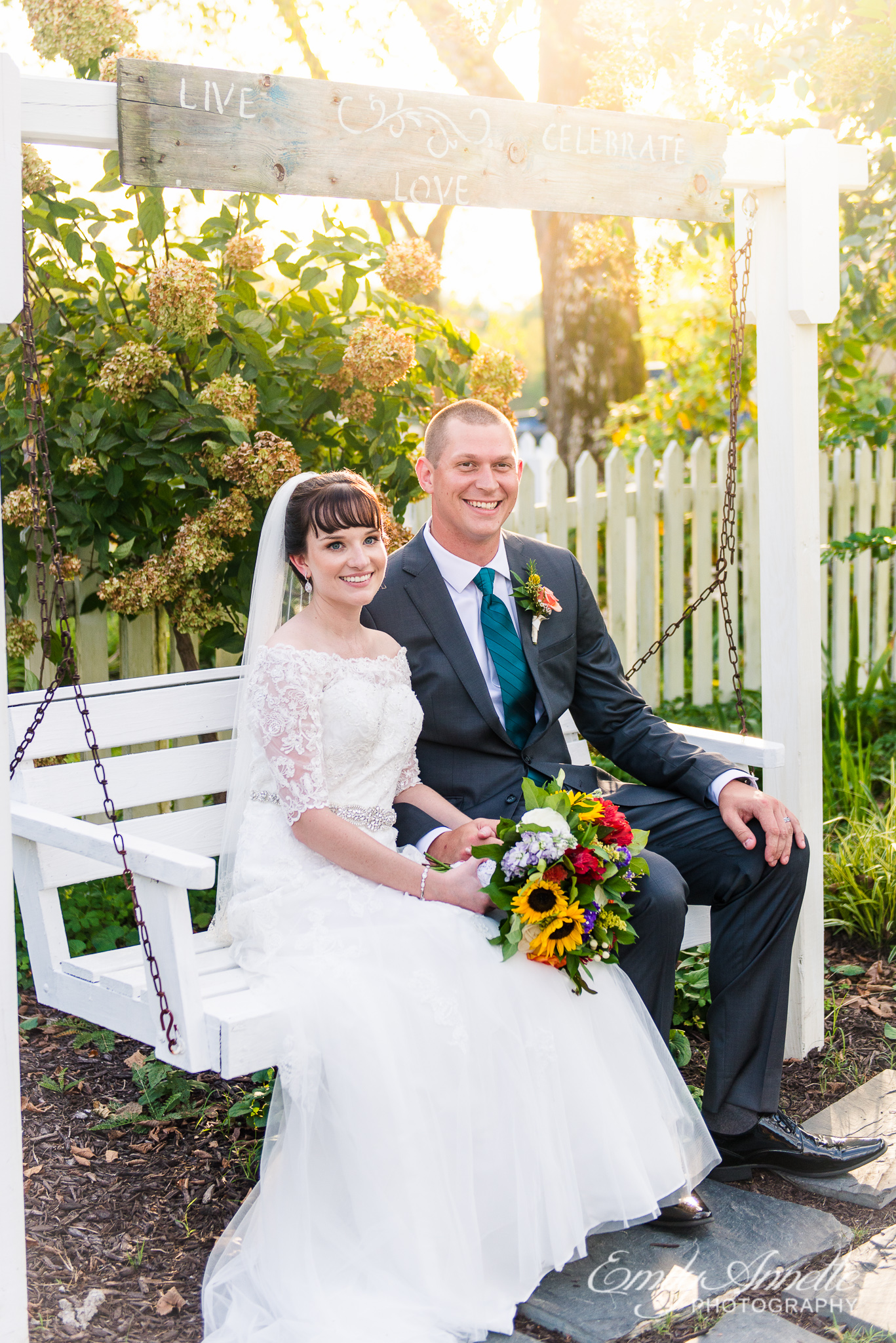 A bride and groom smile at the camera while sitting together on a porch swing during their country wedding at Amber Grove near Richmond, Virginia
